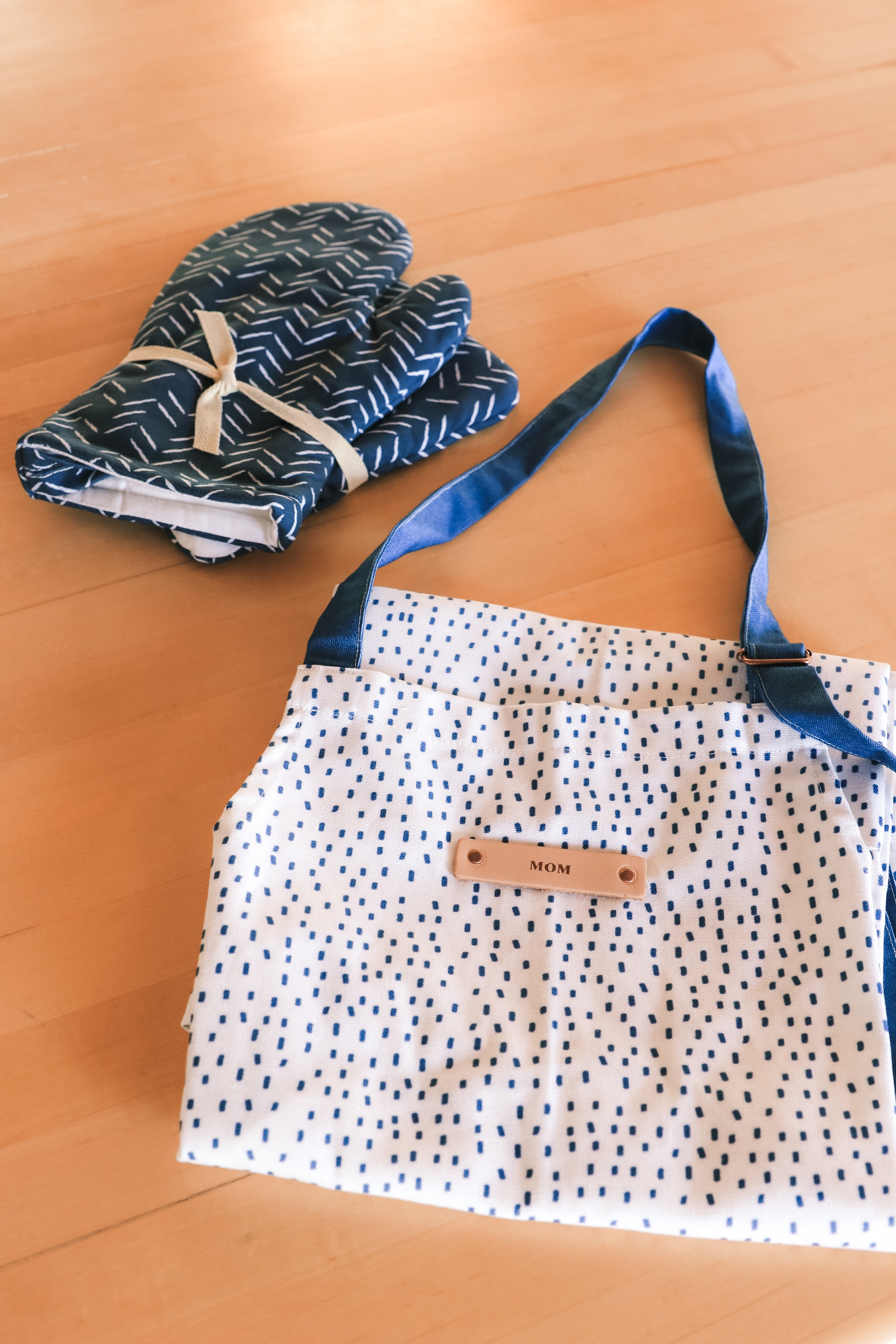 """Personalized Gifts, Erin Busbee of Busbee Style sharing a blue herringbone mitt and potholder set and blue and white speckled apron with """"mom"""" from Minted in Telluride, Colorado"""