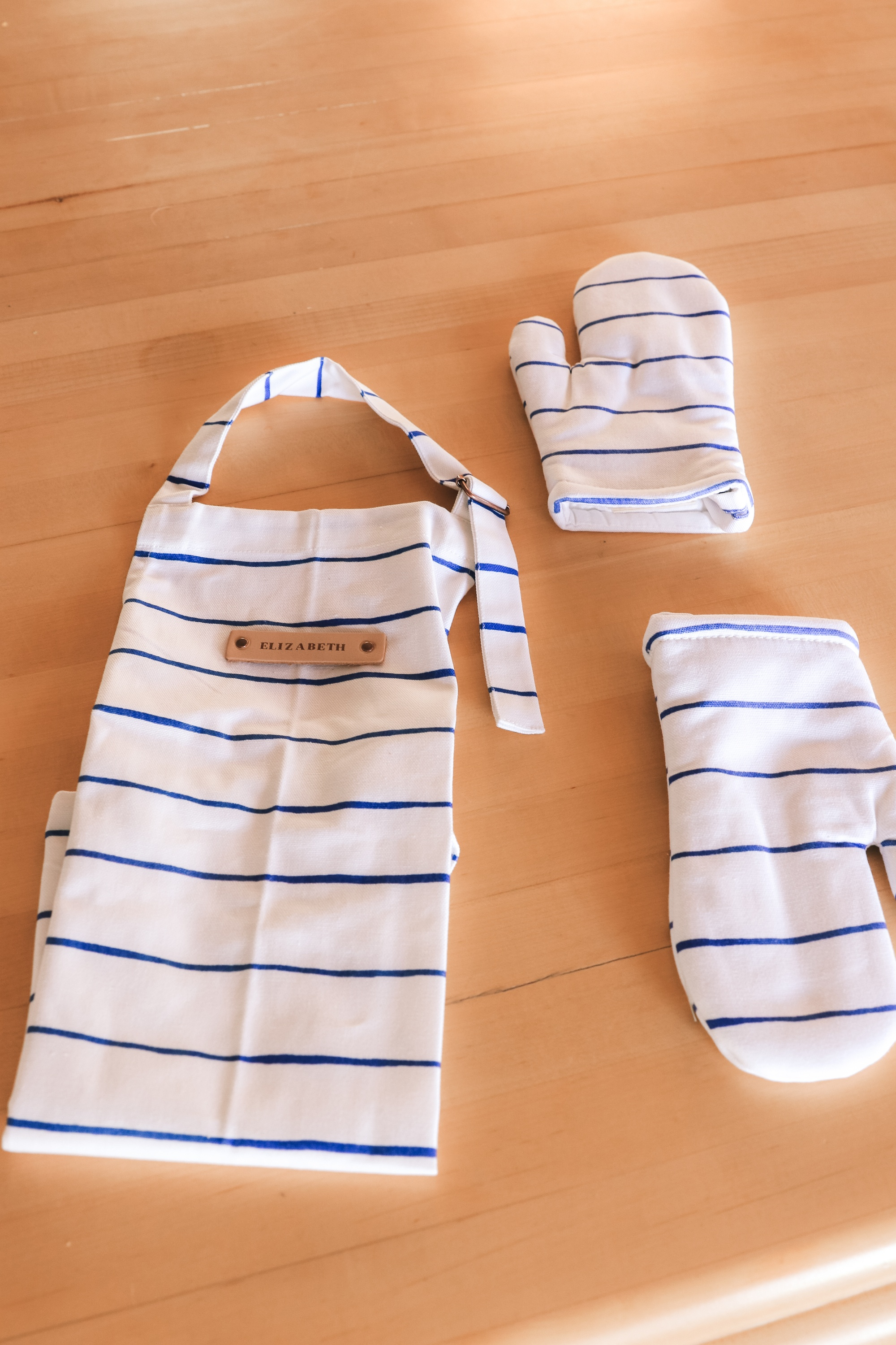 """Personalized Gifts, Erin Busbee of Busbee Style sharing a blue and white striped apron with """"Elizabeth"""" on it for her daughter and matching blue and white striped oven mitts from Minted for her daughter in Telluride, Colorado"""
