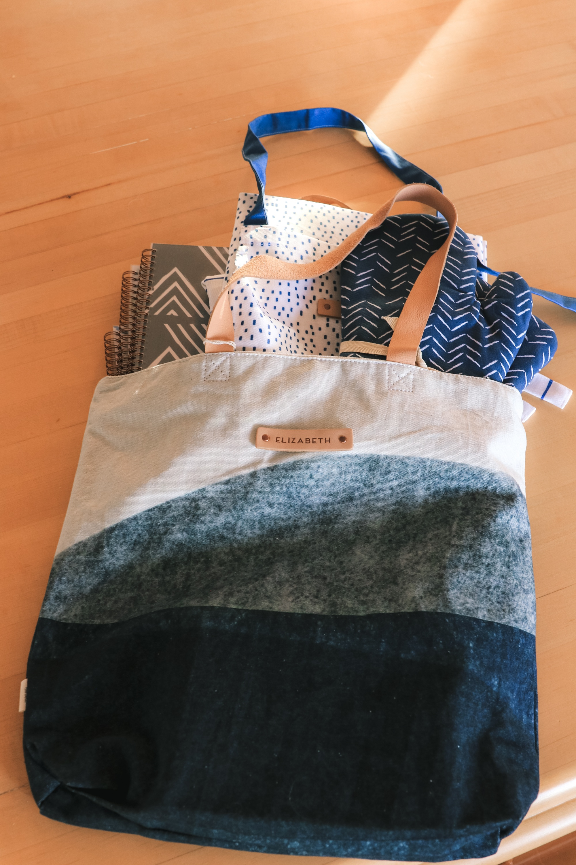 Personalized Gifts, Erin Busbee of Busbee Style sharing a blue and white personalized tote bag with three personalized planners, oven mitts, and aprons from Minted in Telluride, Colorado