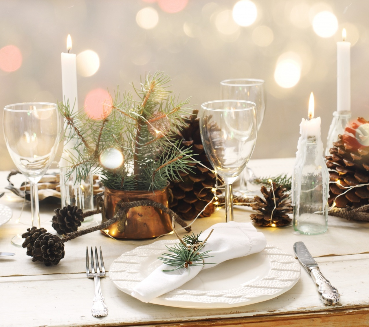Hostess gifts that aren't boring showing a holiday table scape with pinecones, candles and dinner ware
