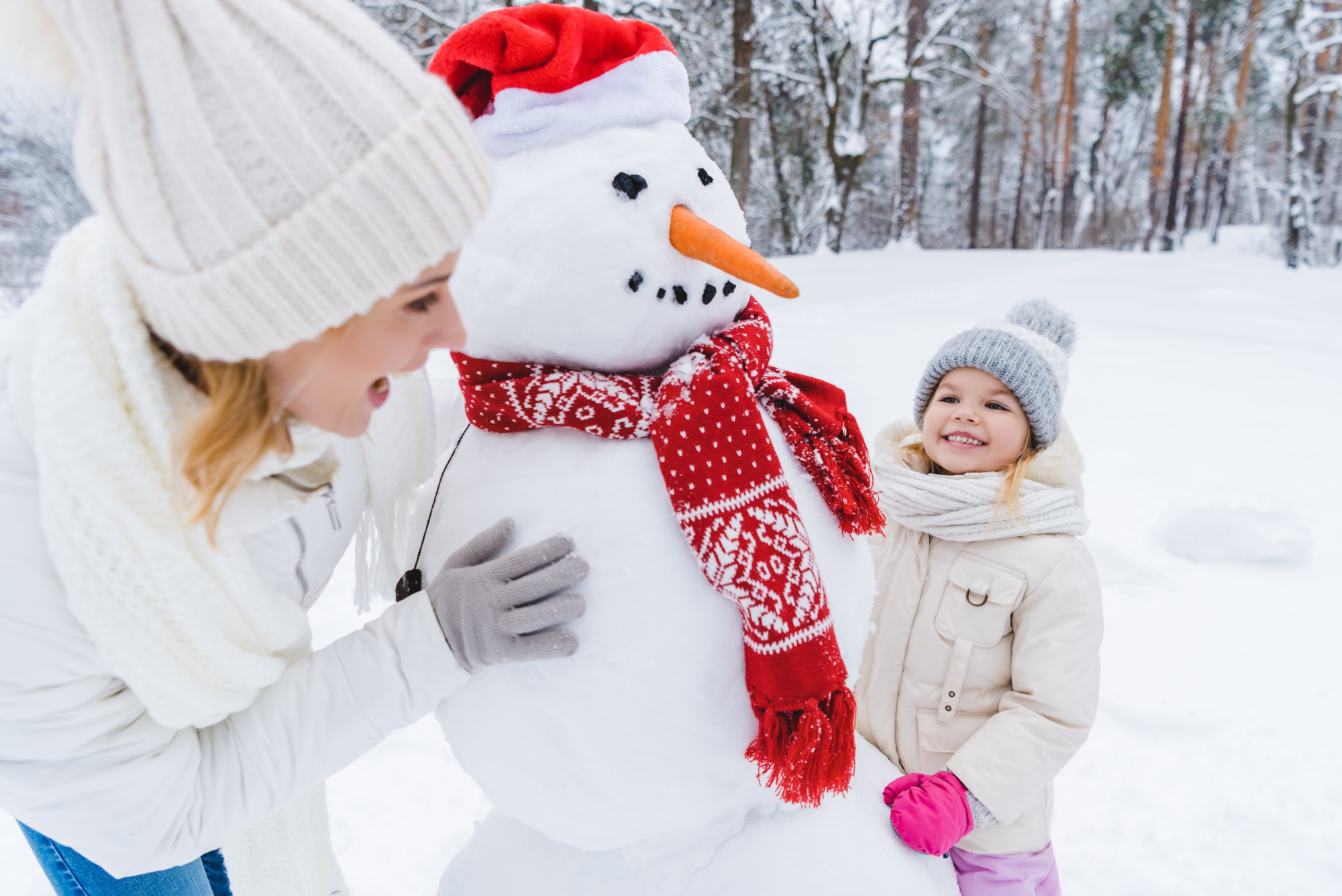 benefits of being outside during winter, happy mother and daughter playing with snowman in winter park