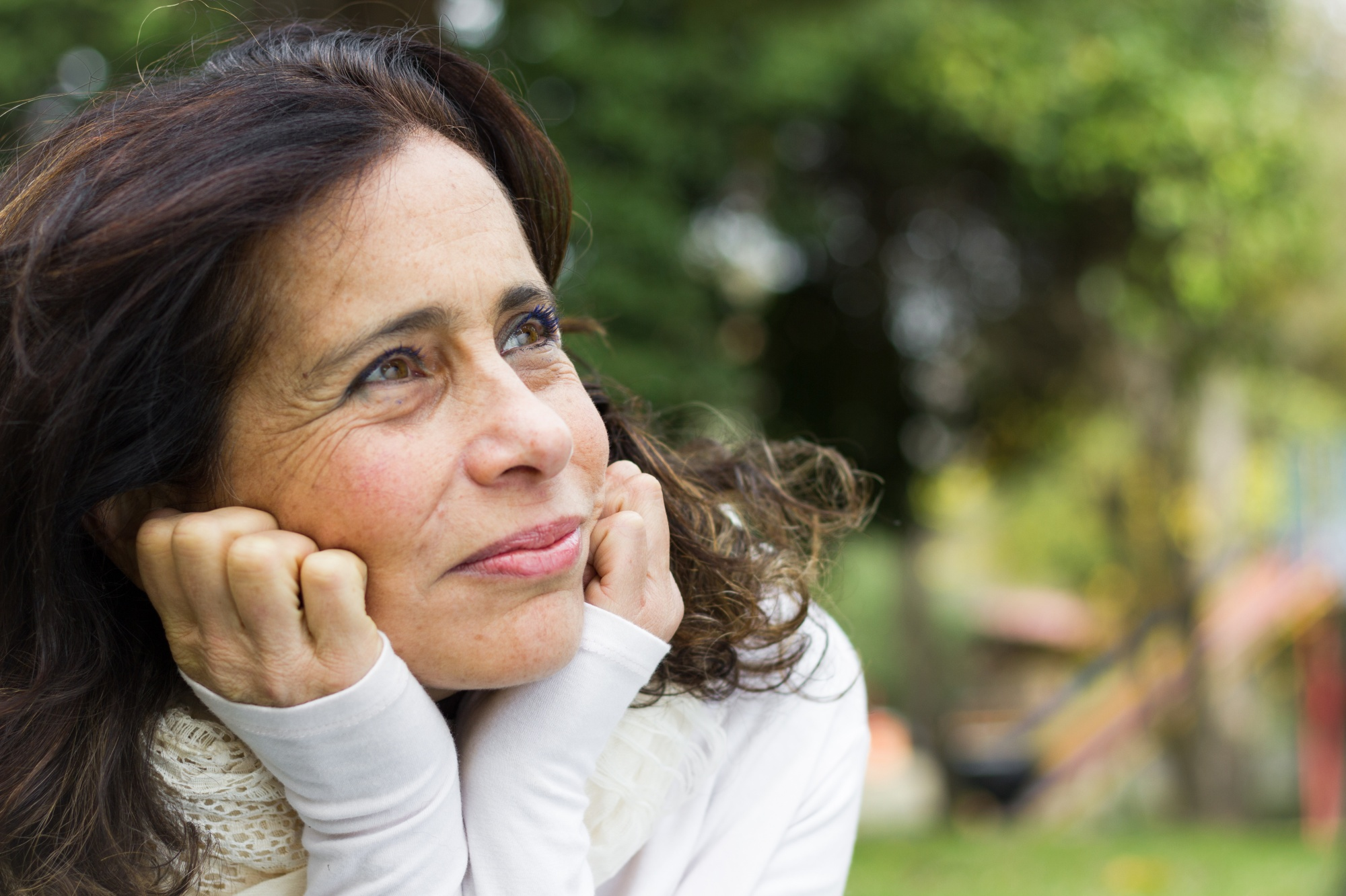 Starting a self care routine, Portrait of middle aged woman with face resting on hands and visionary look. Closeup on pretty mature lady looking up thoughtful with positive expression
