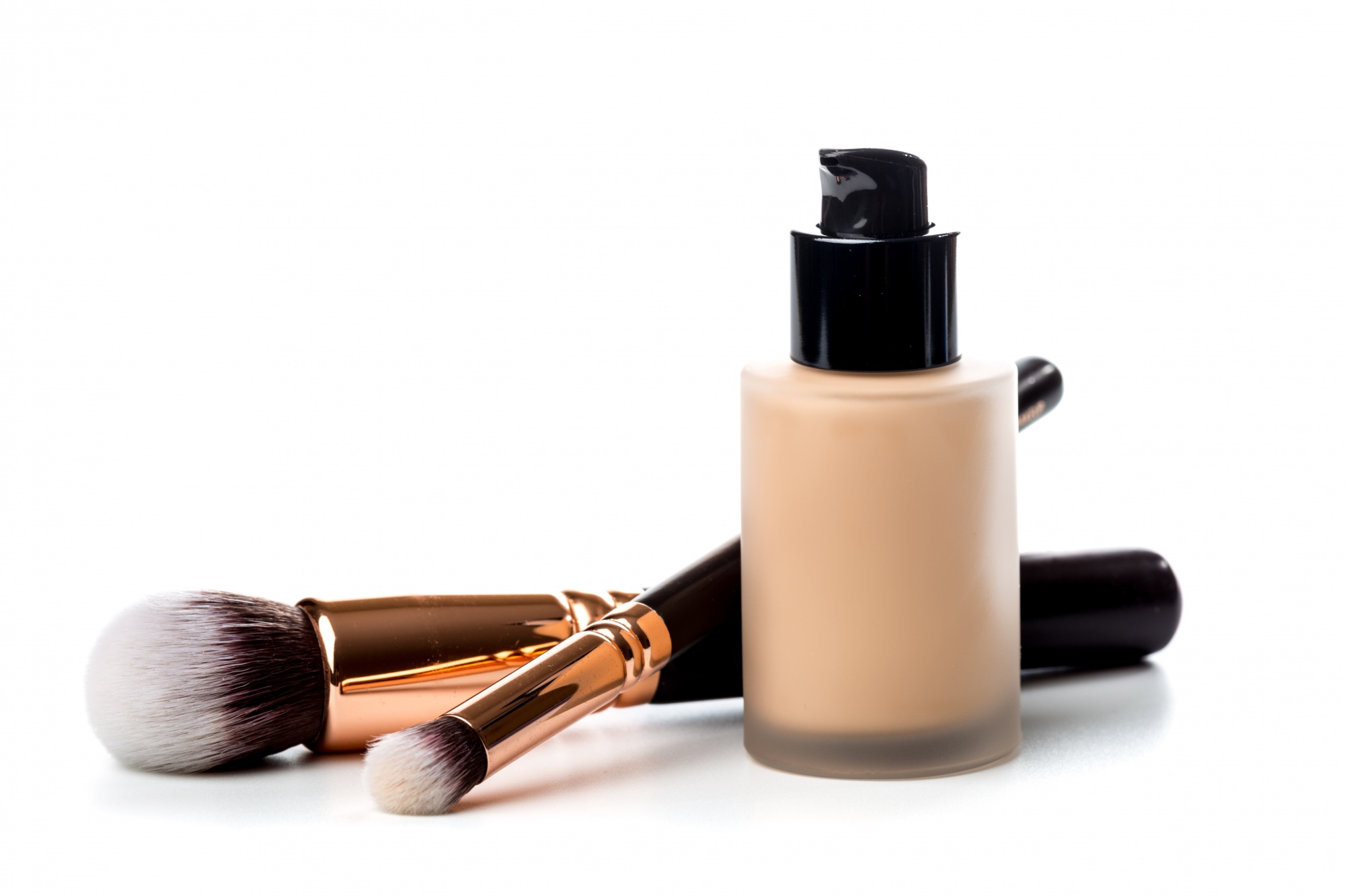 Finding the best foundation for you Close-up of flat makeup brush with liquid foundation tube isolated on white