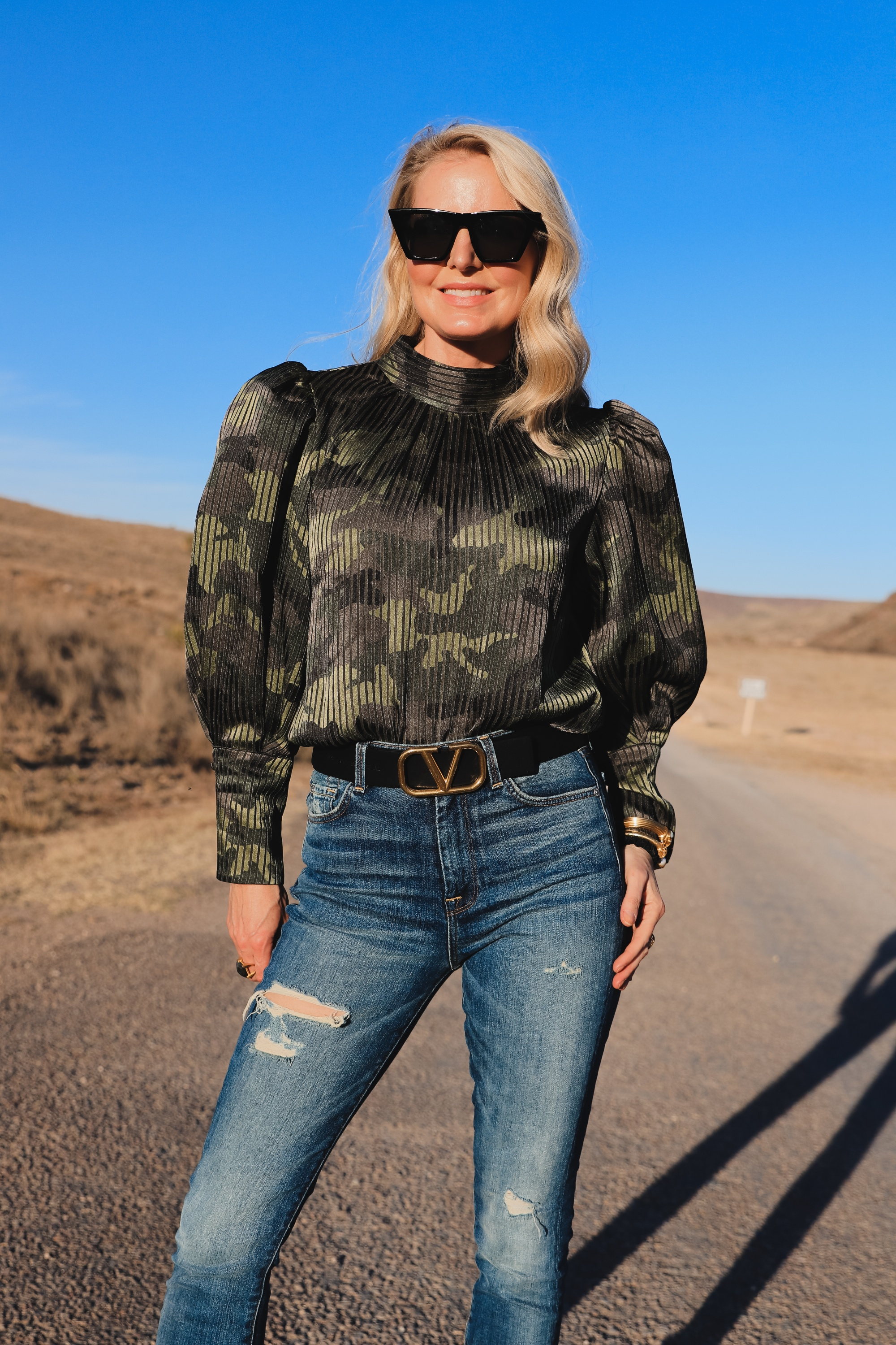 How To Mix Styles, Blogger Over 40 Erin Busbee of Busbee Style wearing a camo puff sleeve top by Alice + Olivia with 7 for All Mankind ripped skinny jeans, Alexander Wang cutout heel booties, black cat eye sunglasses, gold julie vos cuff bracelets, monica vinader diamond ring, and dean davidson cocktail ring in west Texas