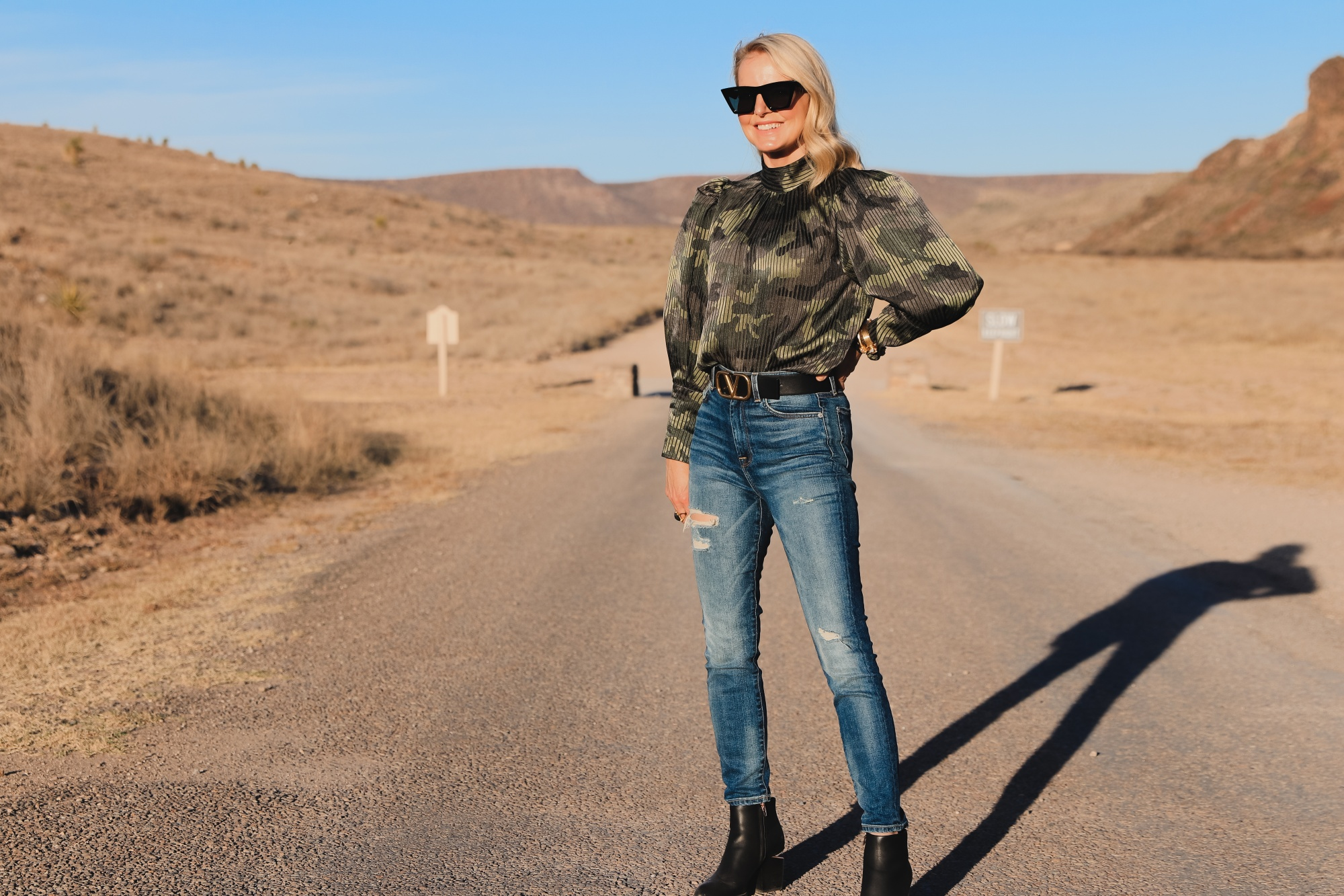 How To Mix Styles, Blogger Over 40 Erin Busbee of Busbee Style wearing a camo puff sleeve top by Alice + Olivia with 7 for All Mankind ripped skinny jeans, Alexander Wang cutout heel booties, black cat eye sunglasses, gold julie vos cuff bracelets, monica vinader diamond ring, dean davidson cocktail ring, and black reversible Valentino belt in west Texas