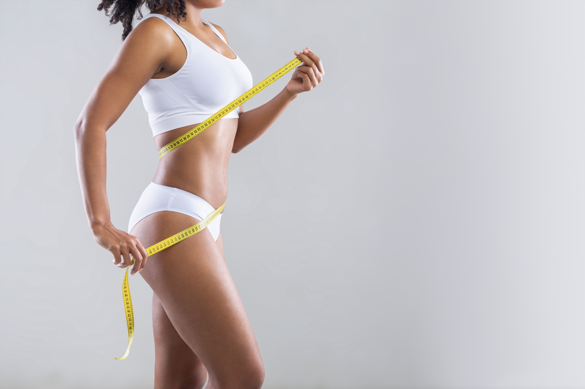 How to Determine Your Body Shape, Erin Busbee sharing how to find your body shape with simple measurements featuring a fit woman in white underwear and bra measuring her body with a yellow measuring tape