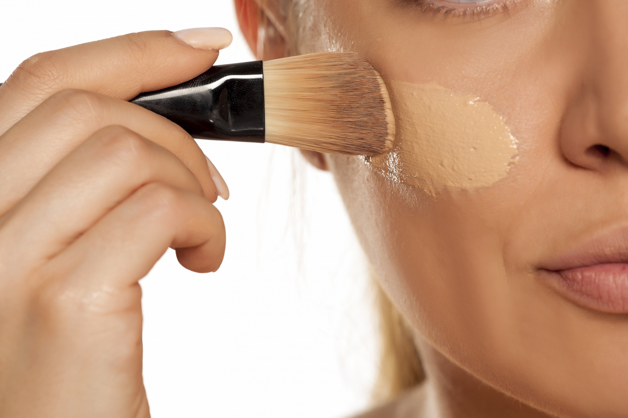 Finding the best foundation for you Young woman applying liquid foundation with brush on white background