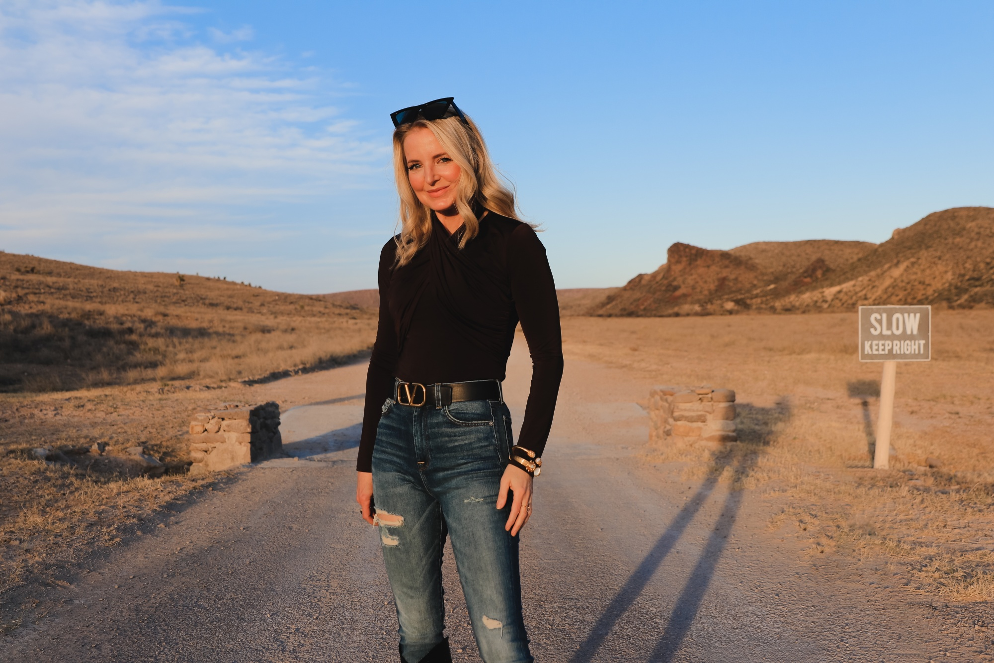Brown and black outfit, Erin Busbee of Busbee Style wearing a dark brown wrapped neck top by Lovers + Friends tucked into 7 for all mankind ripped jeans with black snake-embossed knee-high boots and black reversible Valentino belt in west Texas