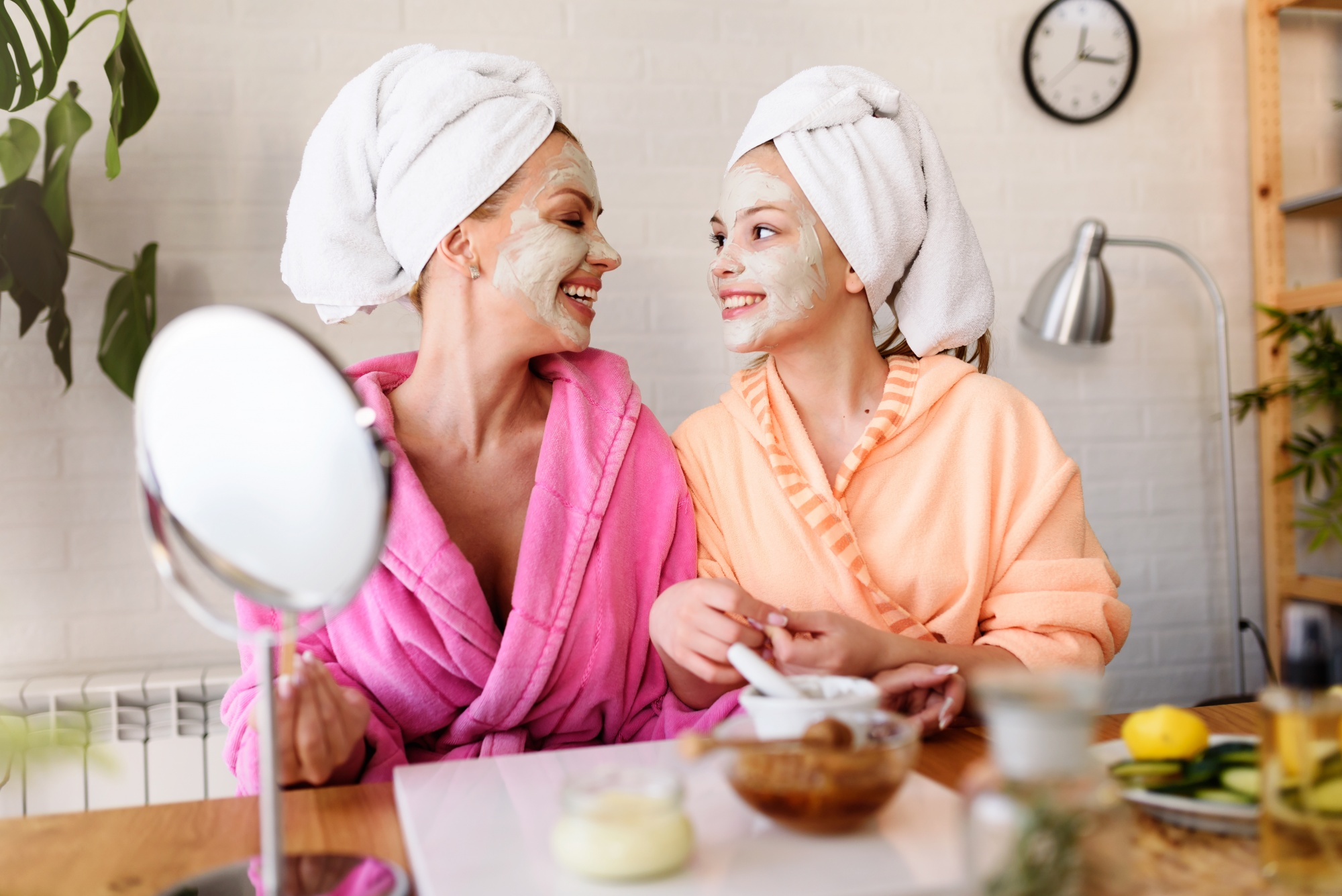 Mother daughter spa day, mom and daughter in bathrobes and towels using natural cosmetics and having fun at home