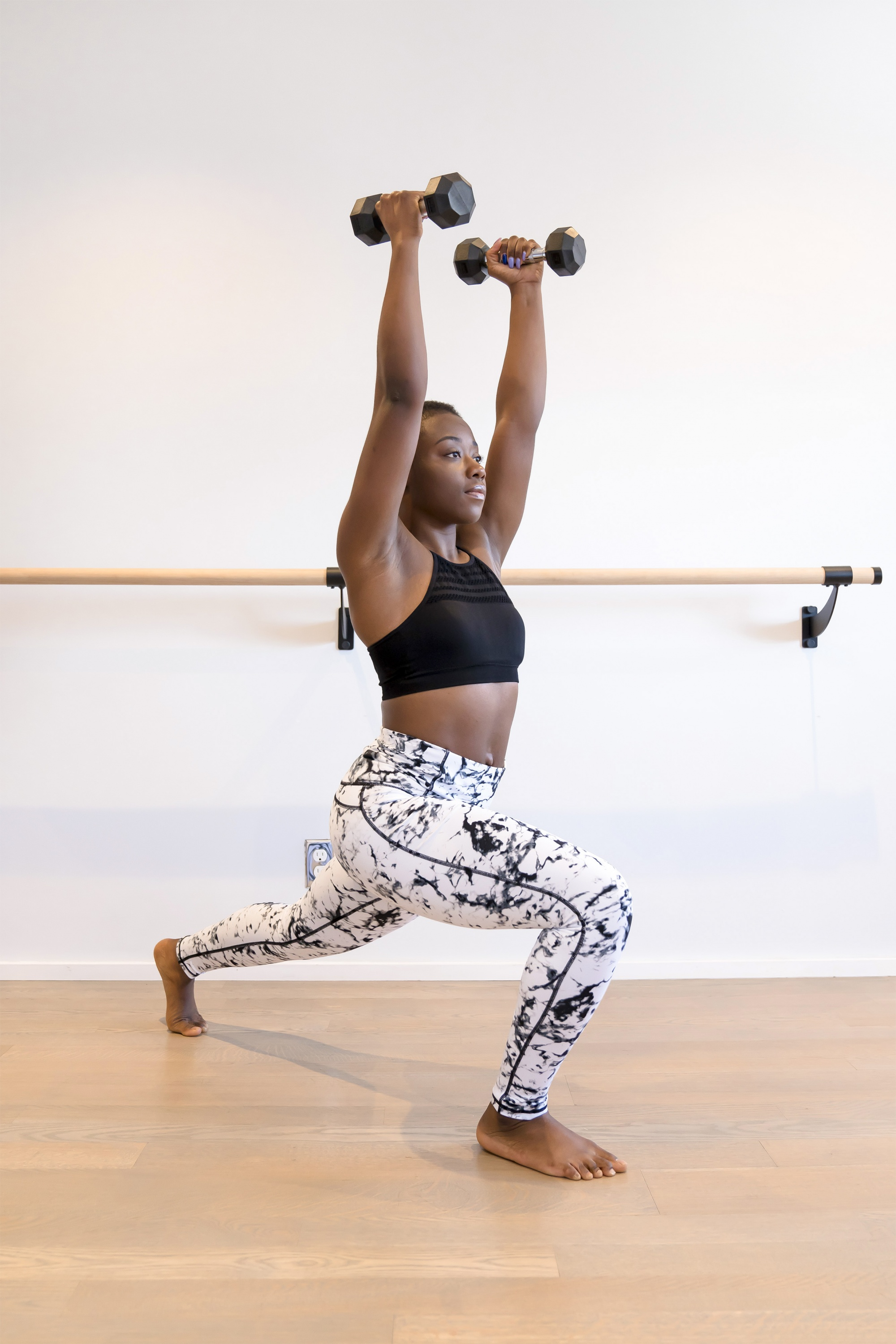 how to get fit over 40, Black woman in b&w leggings and black longline crop top with dumbbells above her head in lunge