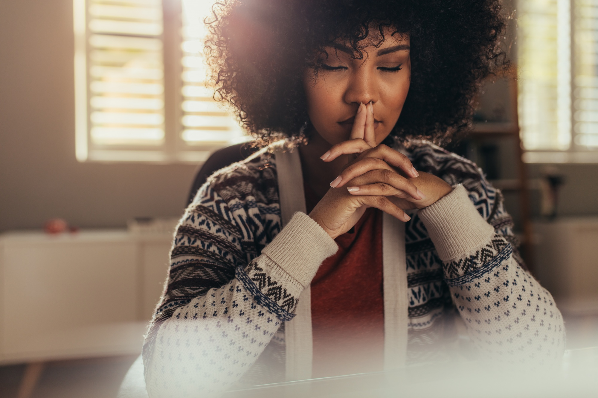 Embrace negative thoughts and turn them into joy, Black woman with eyes closed thinking in red shirt and fair isle cardigan