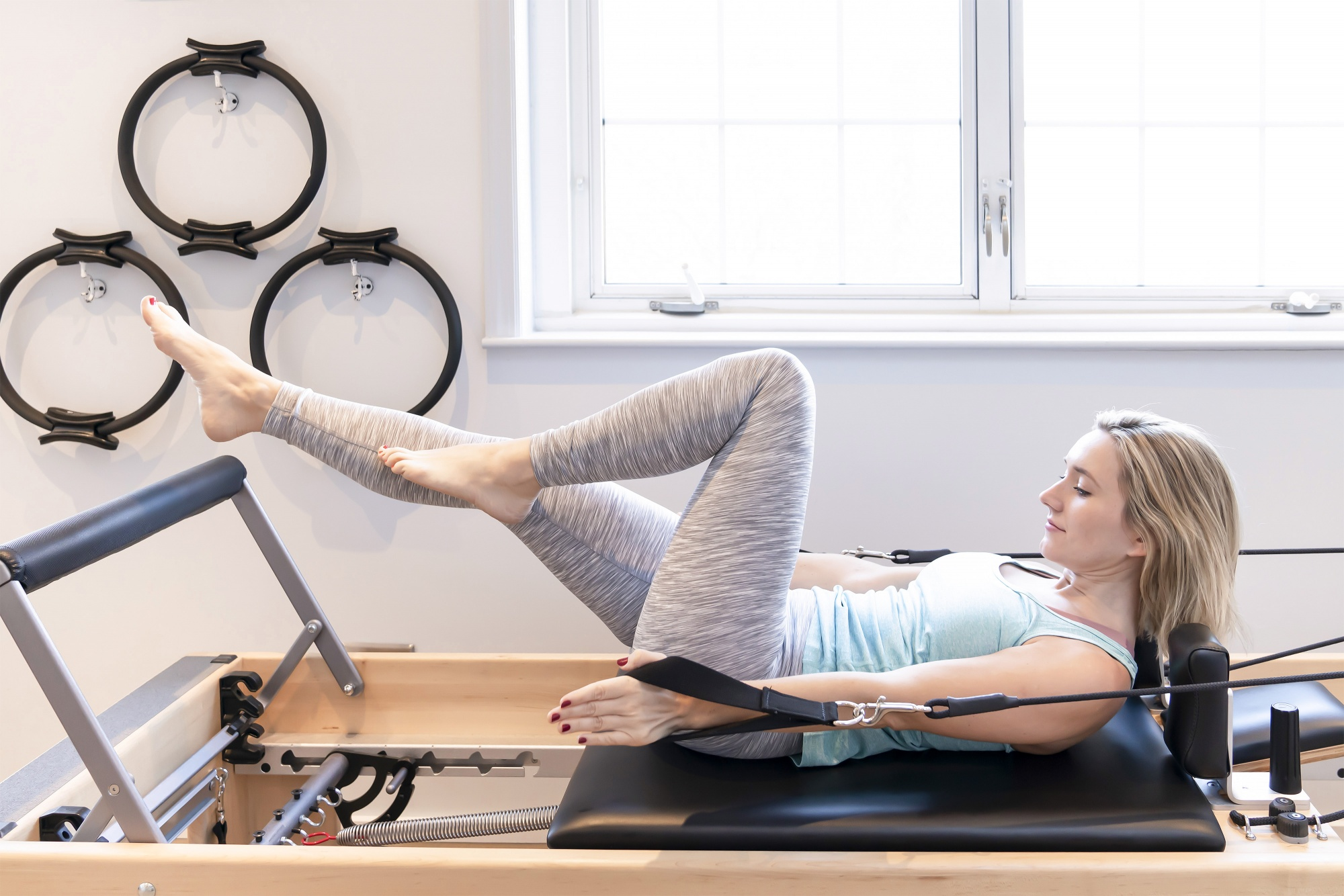 how to get fit over 40, Blonde woman in teal tank and spacedyed grey leggings on Reformer