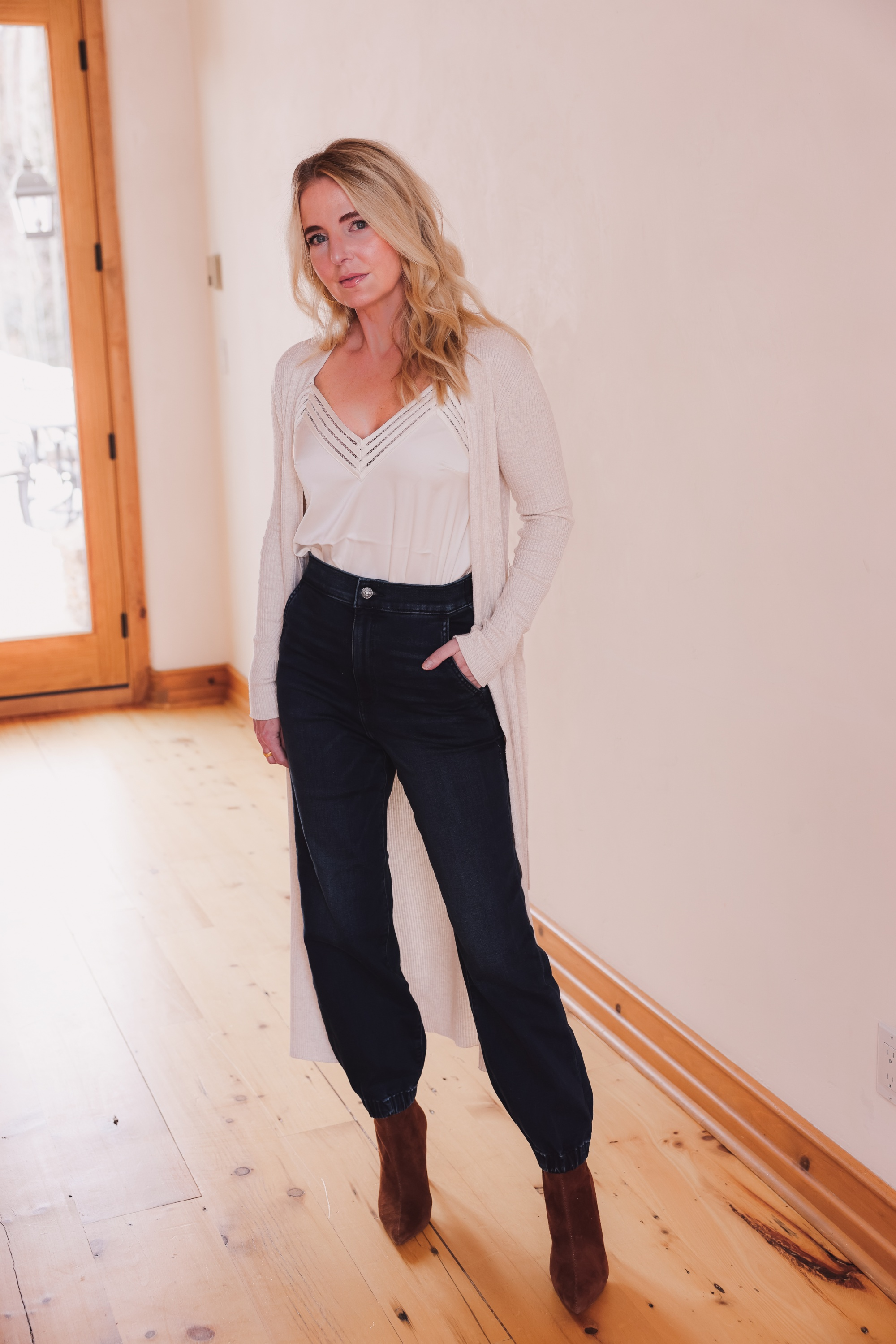 Express Sale, Erin Busbee of Busbee wearing denim joggers, a white satin cami, and long ribbed duster cardigan from Express with Steve Madden brown booties in Telluride, Colorado