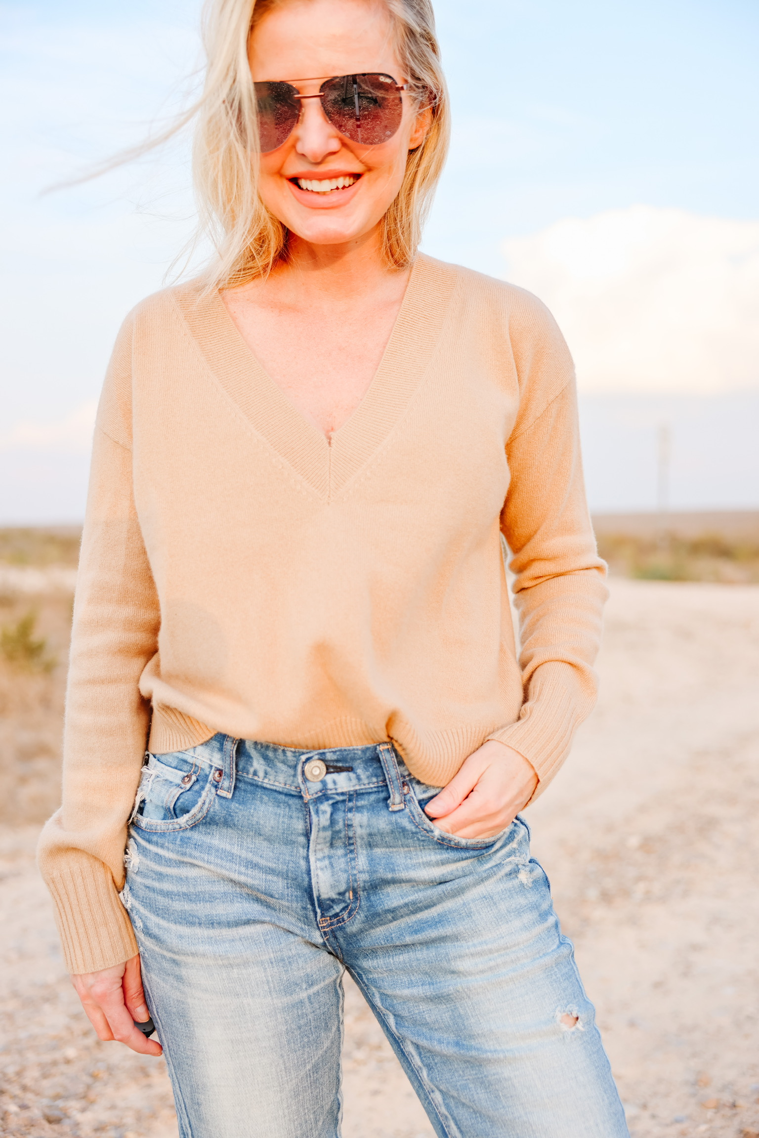 elevated basics, Erin Busbee of Busbee wearing a camel cashmere v-neck sweater from INtermix with distressed skinny jeans by Moussy Vintage and white golden goose sneakers in south Texas