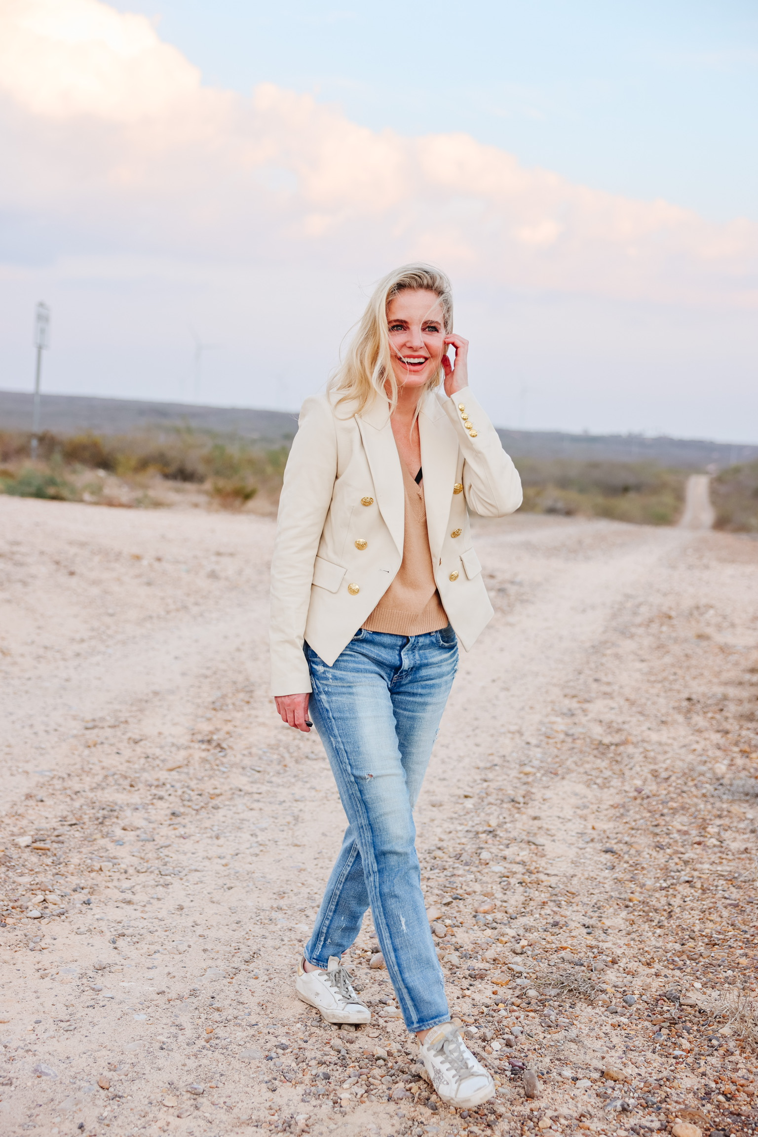 White and Camel together, Erin Busbee of Busbee wearing a white leather veroncia beard cooke blazer over an intermix v-neck camel cashmere sweater with moussy vintage skinny jeans and golden goose sneakers in south texas