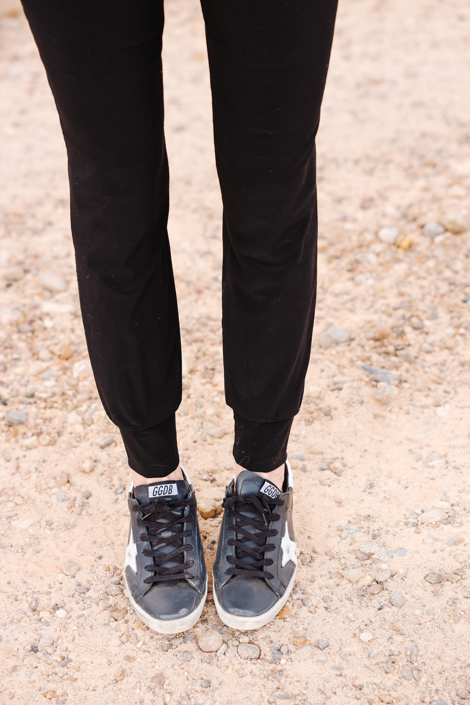 Elevated Basics, Erin Busbee of Busbee wearing black golden goose sneakers with black joggers by Norma Kamali in south texas, what shoes to wear with jeans