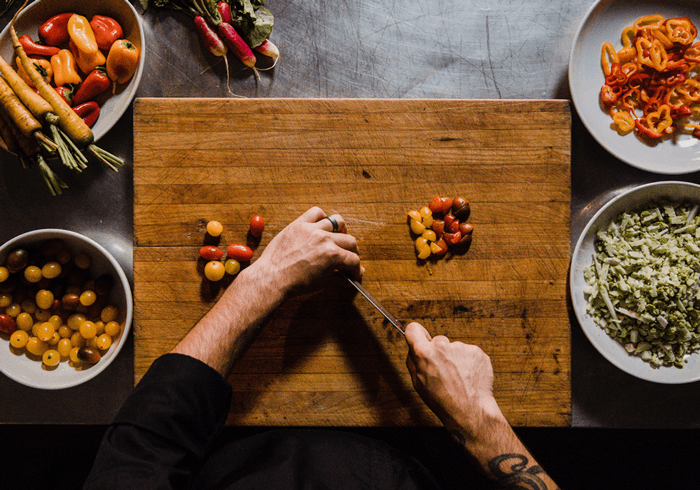best meal delivery services, hands chopping vegetables on a large cutting board