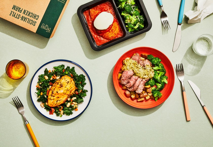 best meal delivery services, white and red dinner plates with entrees, packaged dinner and partial box from Freshly