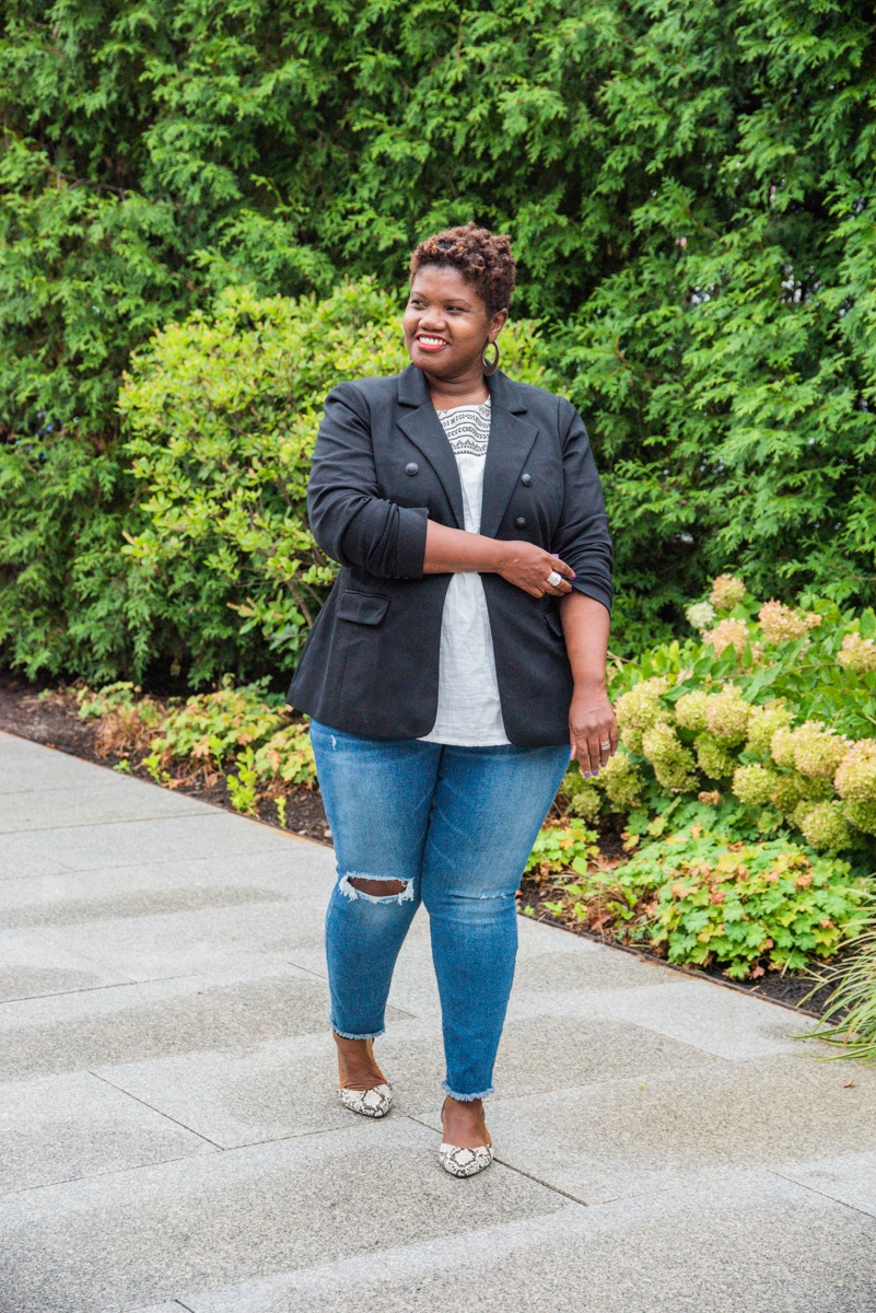 Styling Blazers Over 40, Georgette from Grown & Curvy Woman wearing a classic blazer and jeans outfit with snake print flats and gray top