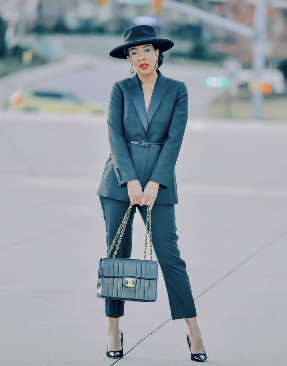 Styling Blazers Over 40, Stephanie from Haute Grey Fox wearing a belted blazer with black trousers, black pumps, a black hat, and black Chanel bag