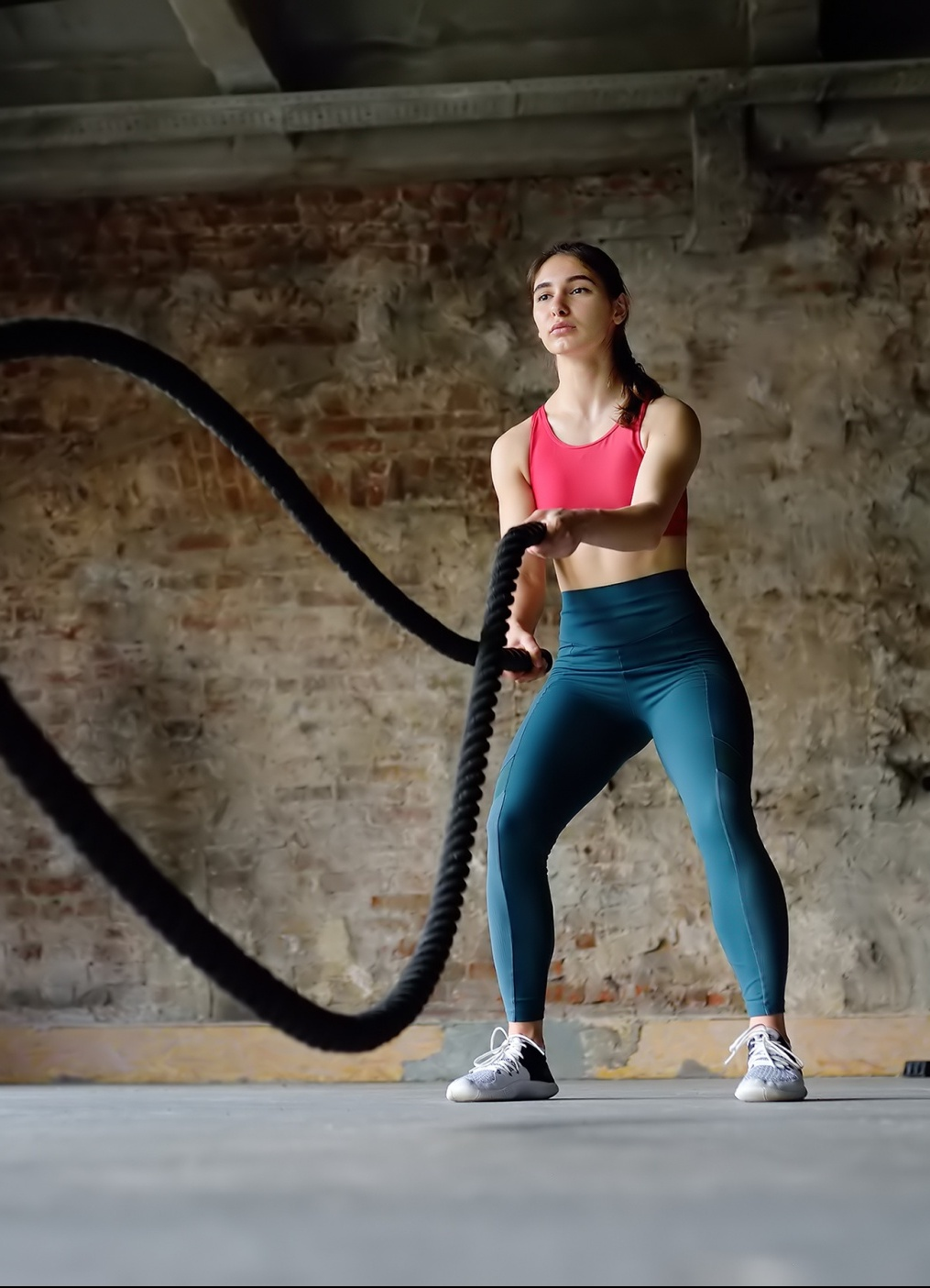 most effective exercise methods for women over 40, long dark-haired woman in bright pink sports bra and teal leggings with battle ropes