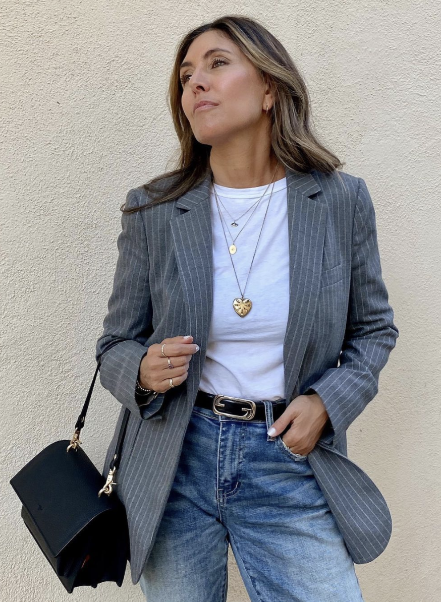 Styling Blazers Over 40, Melissa Meyers from The Glow Girl wearing a gray pinstripe blazer with white tee, jeans, black bag, and simple gold jewelry