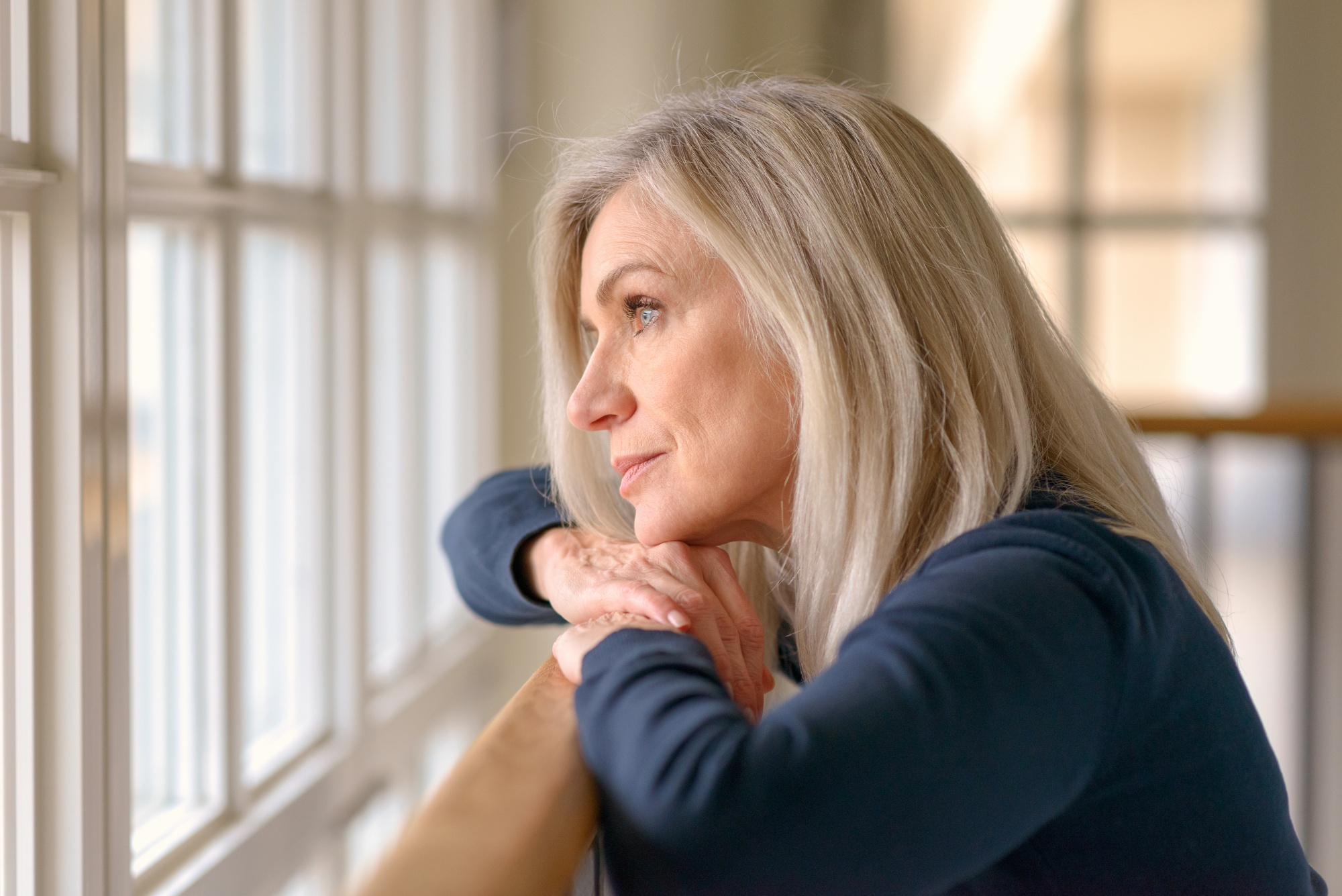 Embrace negative thoughts and turn them into joy, Middle-aged blonde woman in blue shirt looking out window a little sad