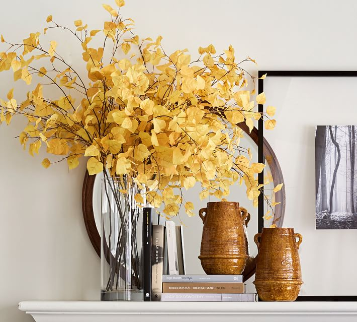 Revealing Pantone's 2021 colors of the year illuminating yellow and ultimate grey with yellow flower stems in a glass vase on a white fireplace mantel