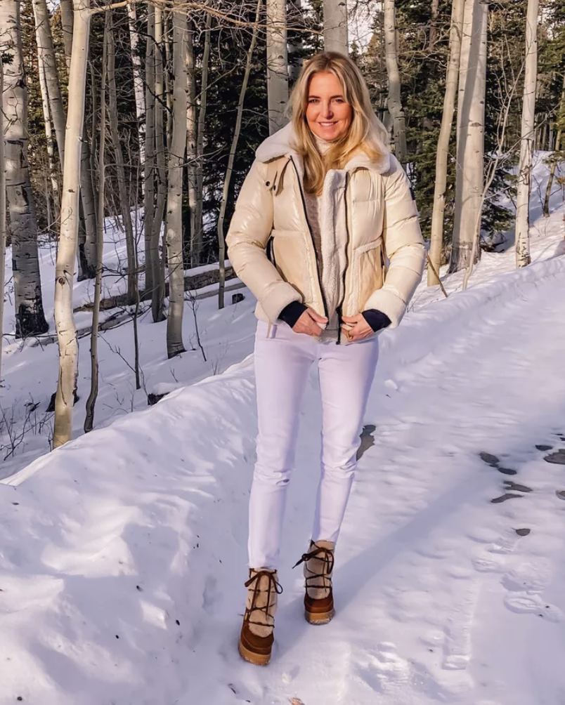 January Best Sellers, Erin Busbee of Busbee wearing a cream colored SAM. shearling puffer jacket with white jeans, cable knit sweater by Vince, and brown shearling boots by See By Chloé in the snow in Telluride, Colorado