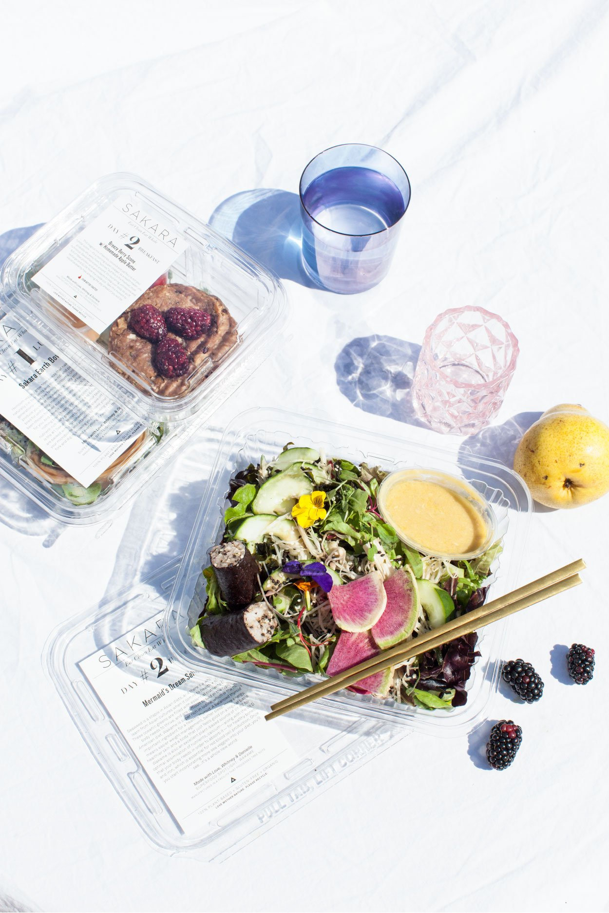 best meal delivery services, An open package of Sakara Life meal with chopsticks, two sealed meals, a glass of water and an empty tumbler on a white background