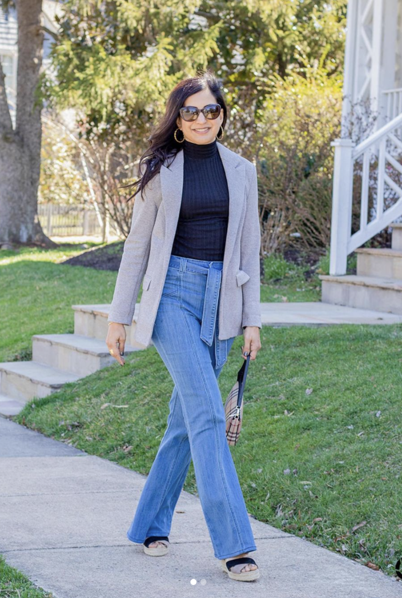 Styling Blazers Over 40, Sapna Delacourt from Lunch with A Girlfriend wearing a long beige blazer with black turtleneck, flared jeans, and wedges