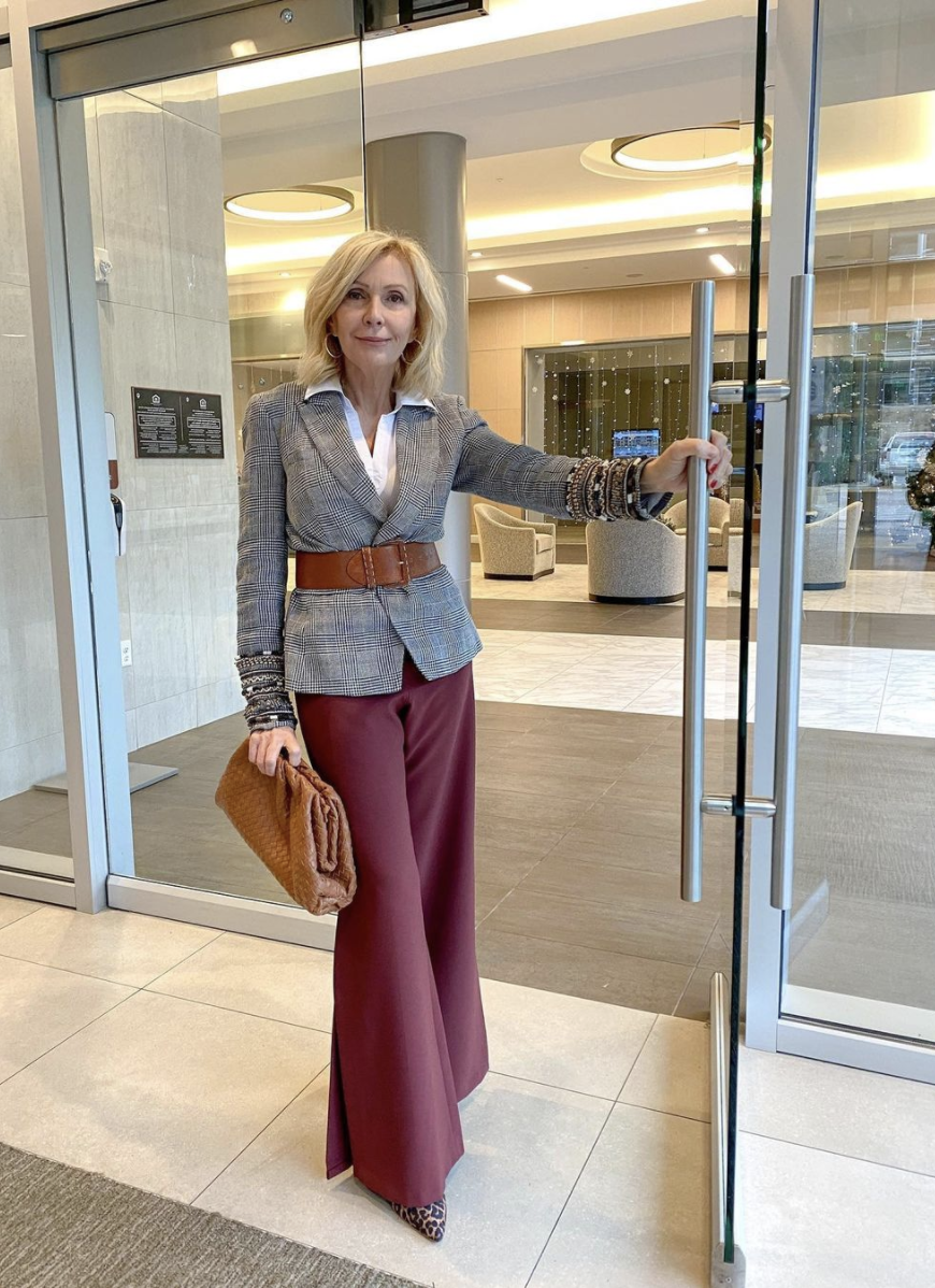 Styling Blazers Over 40, Sonia of Style Beyond Age wearing a belted plaid blazer over a white button down and burgundy wide leg jeans