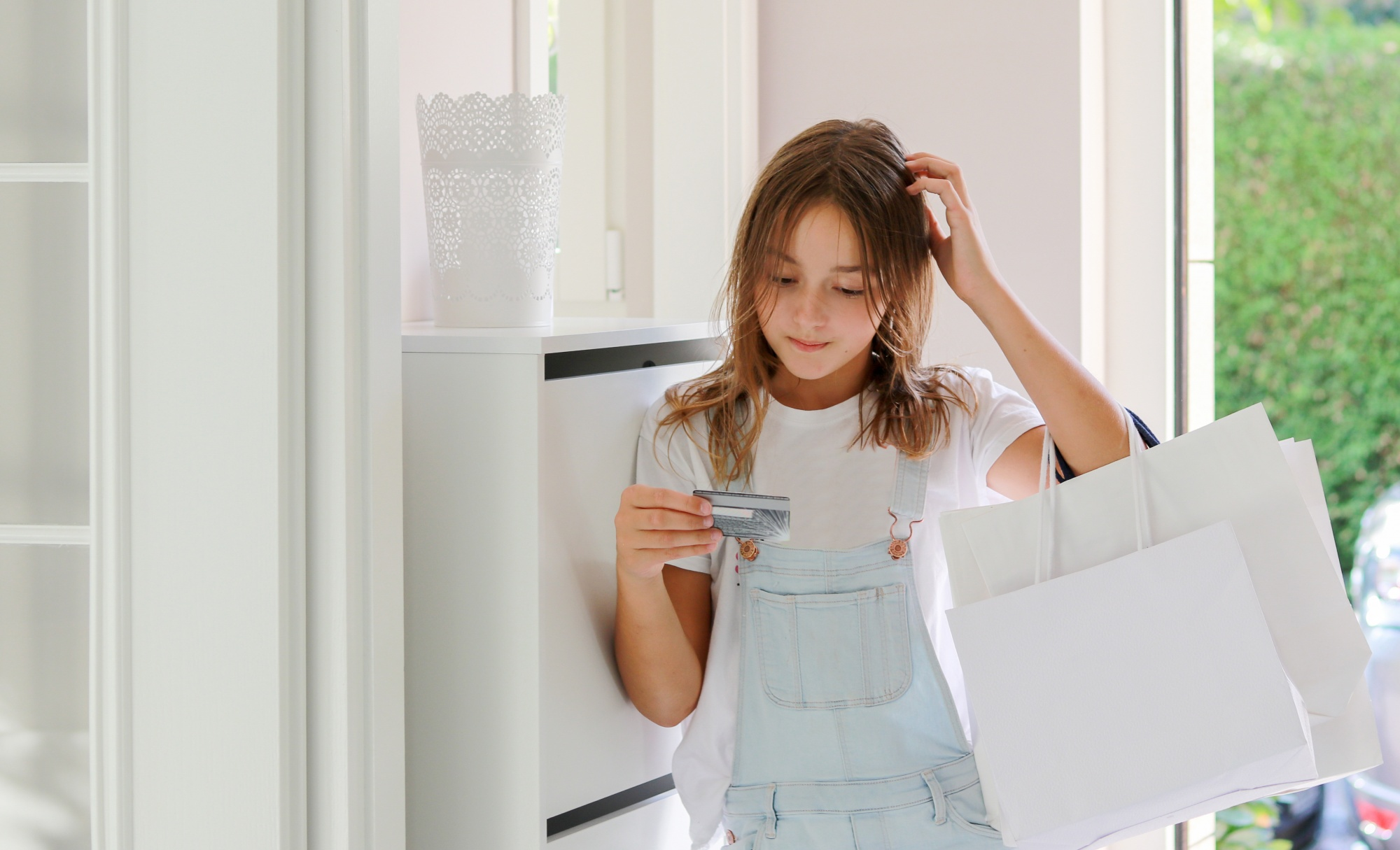 Teaching kids about money, confused tween girl with shopping bags looking at credit card