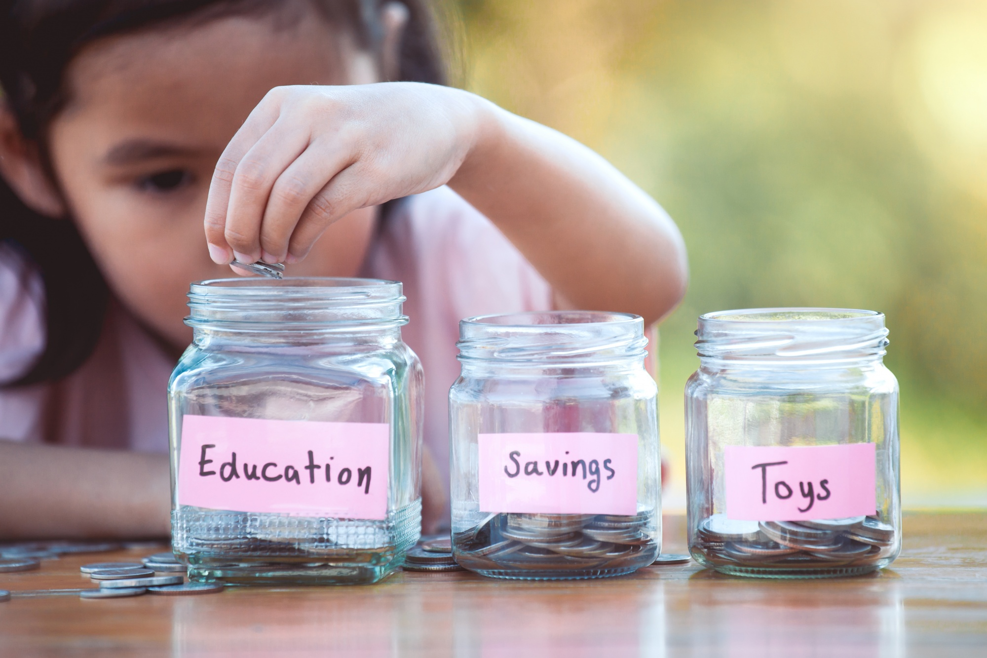 Teaching kids about money, little girl dividing coins into different savings jars