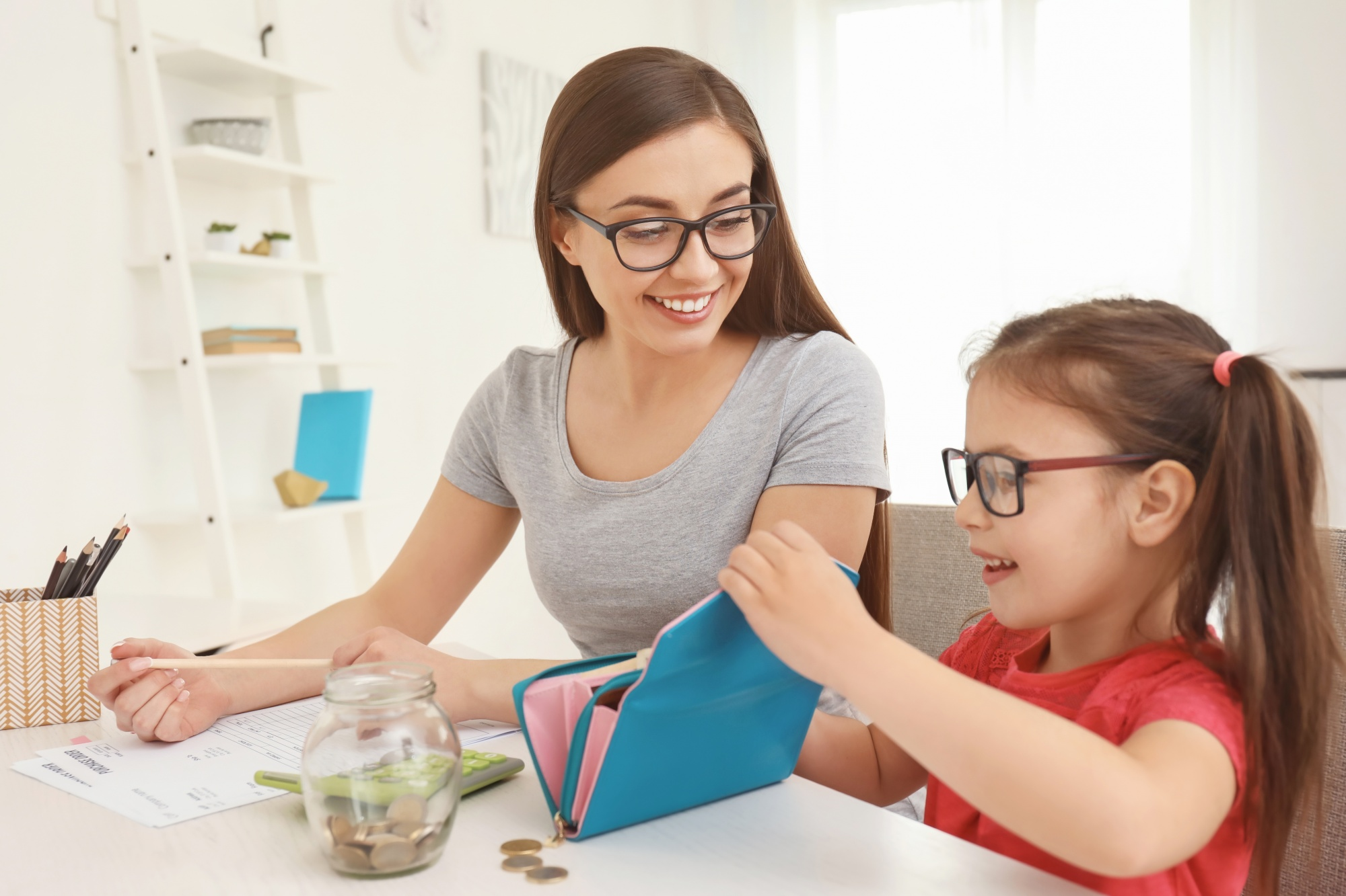 Teaching kids about money, mom and daughter review a budget and money in a wallet together