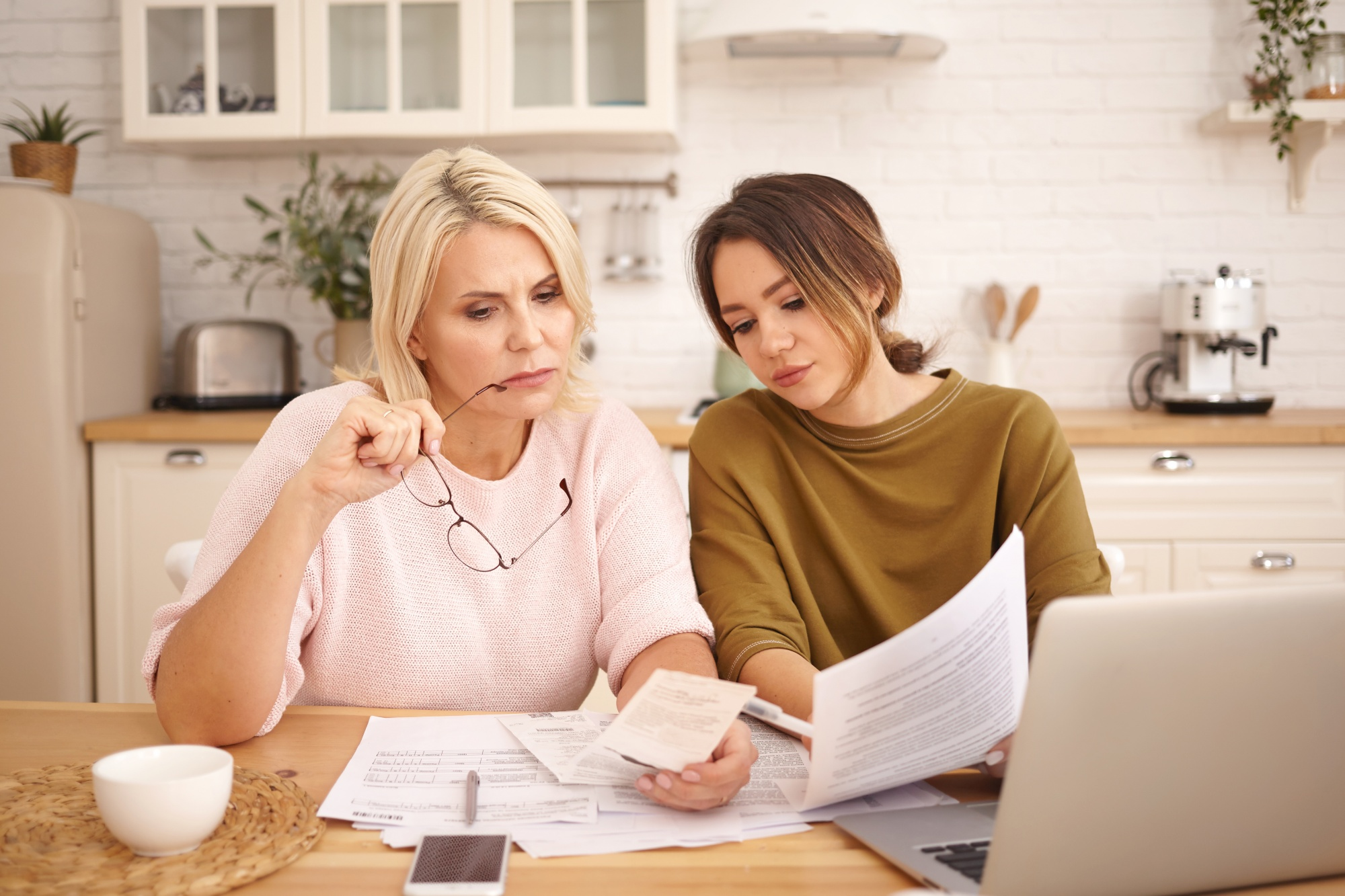Teaching kids about money, mom and teen girl review expenses together at the kitchen table