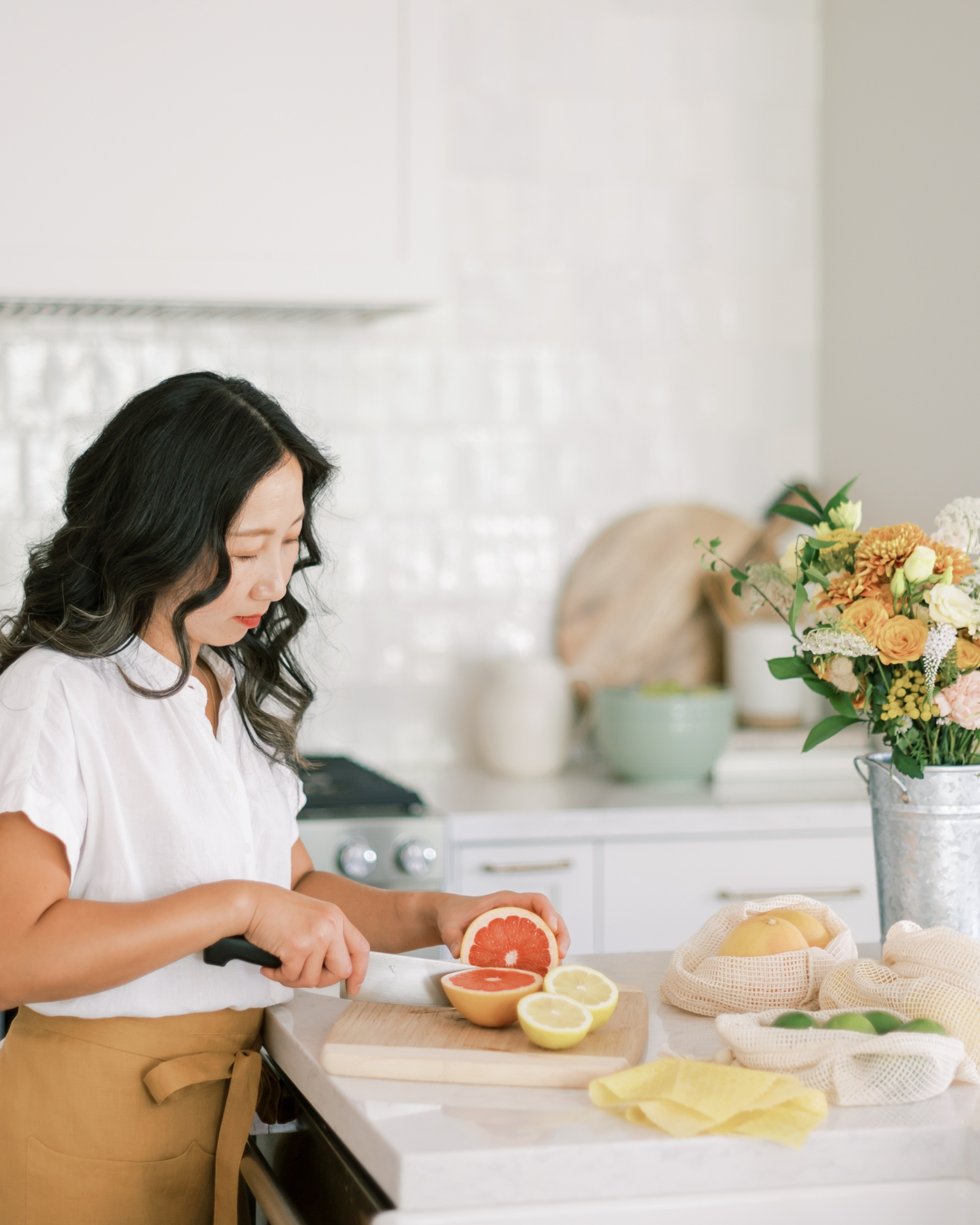 self-care and self-love, asian woman cutting a grapefruit in a white blouse and tan skirt in modern white kitchen