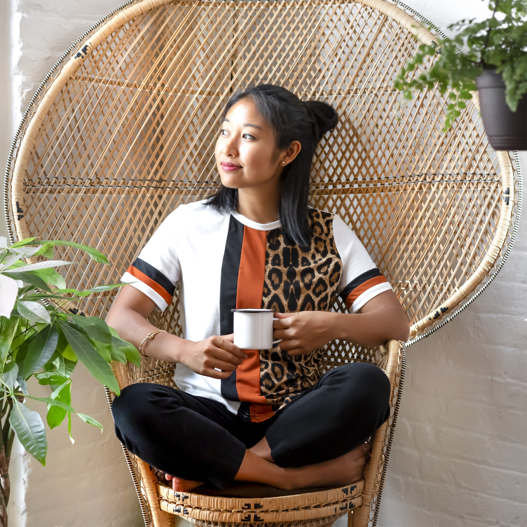self-care and self-love, asian woman sitting crosslegged in rattan chair holding mug and thinking positive thoughts
