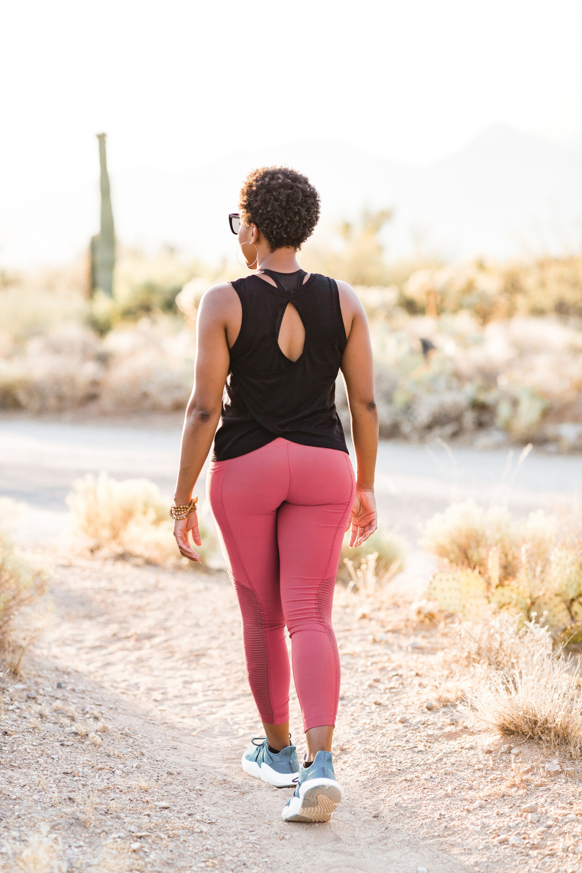 self-care and self-love, black woman from behind in black shirt and pink leggings walking through desert