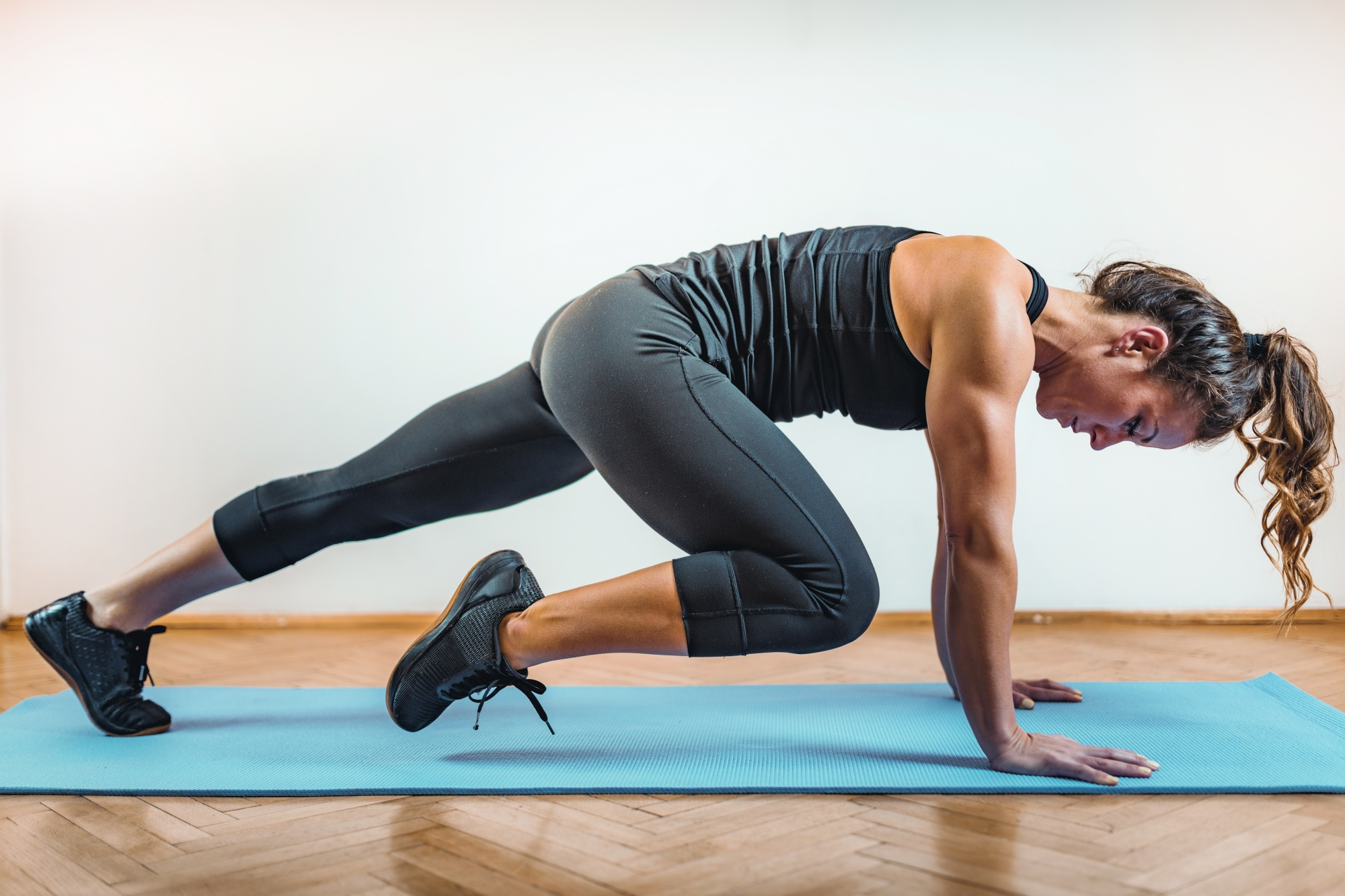 how to get rid of flabby arms, brown-haired woman in black workout clothes in knee-to-elbow plank