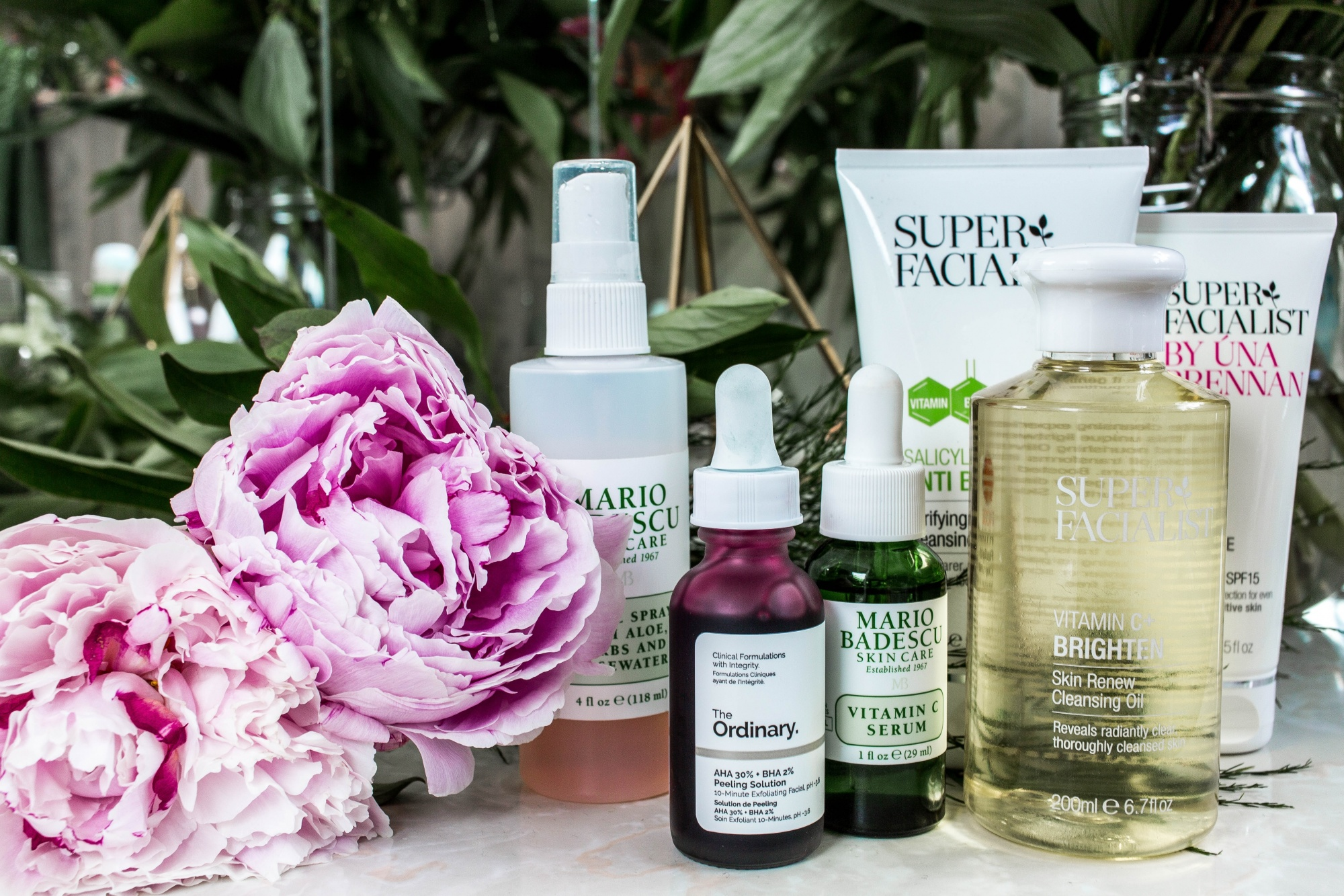 how to reduce hyperpigmentation, hyperpigmentation solutions various bottles on a table with flowers including products by Mario Badescu, The Ordinary, and more
