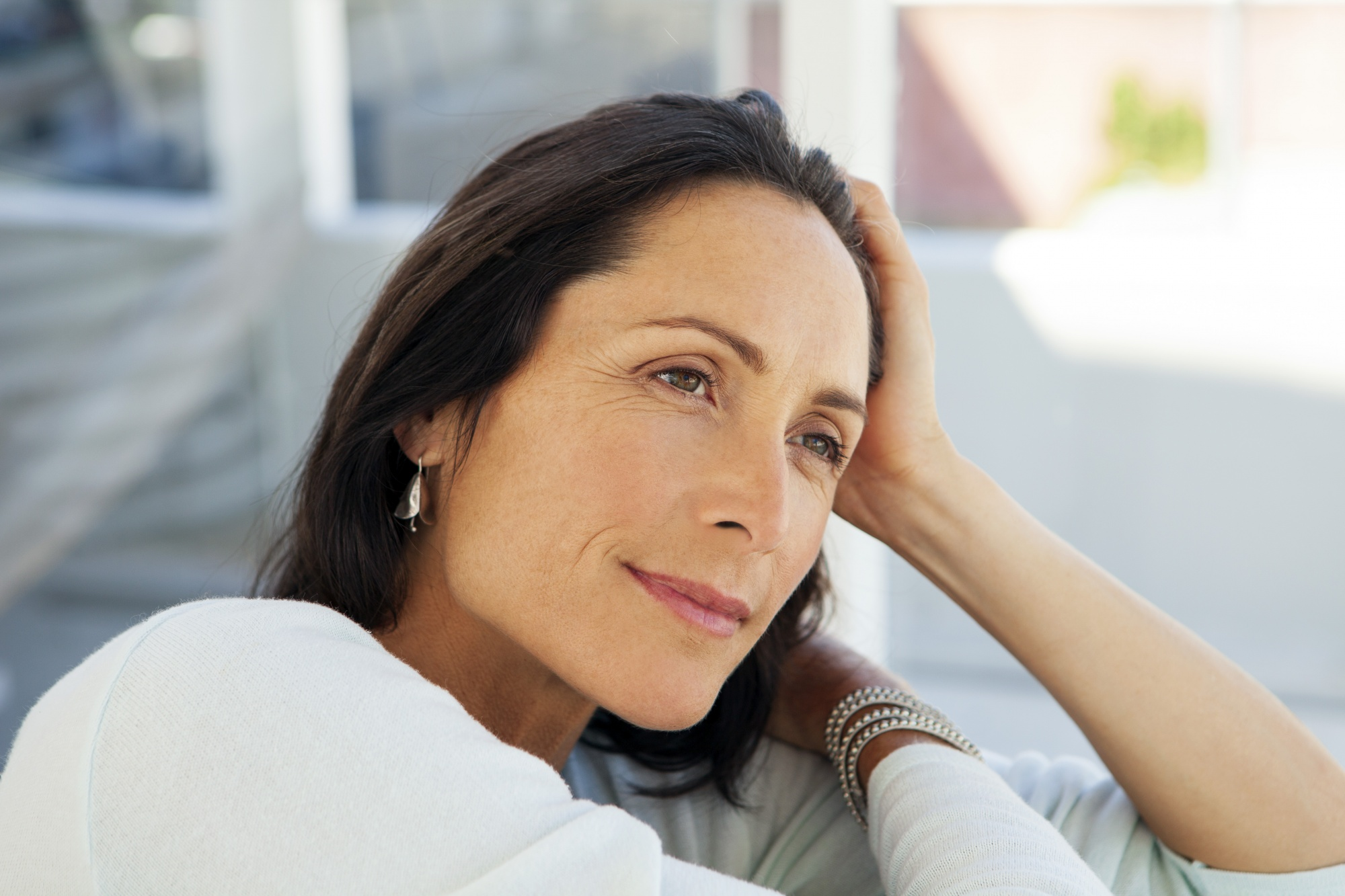 Embrace negative thoughts and turn them into joy, dark-haired middle-aged woman in white shirt thinking