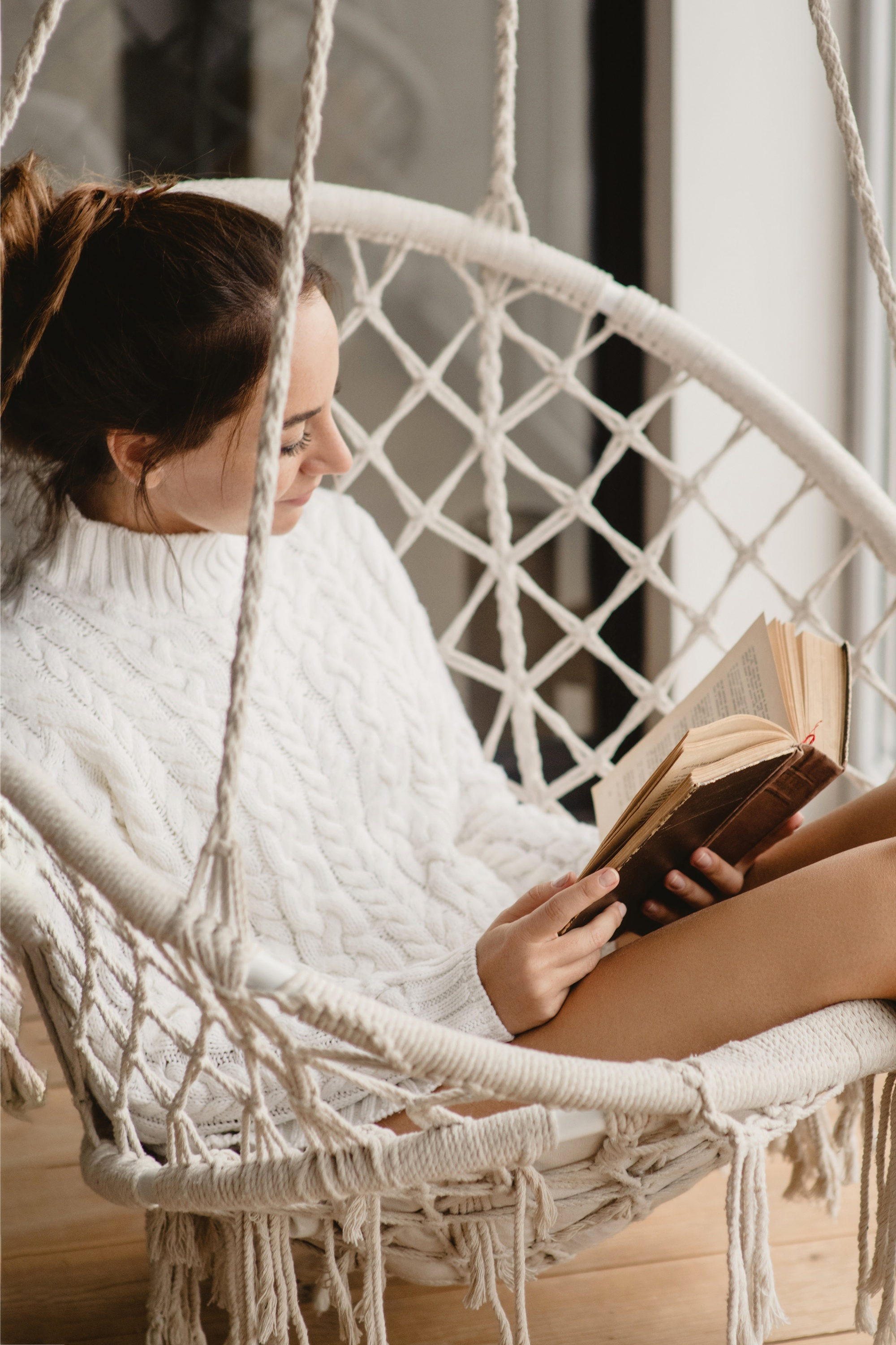 self-care and self-love, woman in cableknit white sweater reading in hammock swing