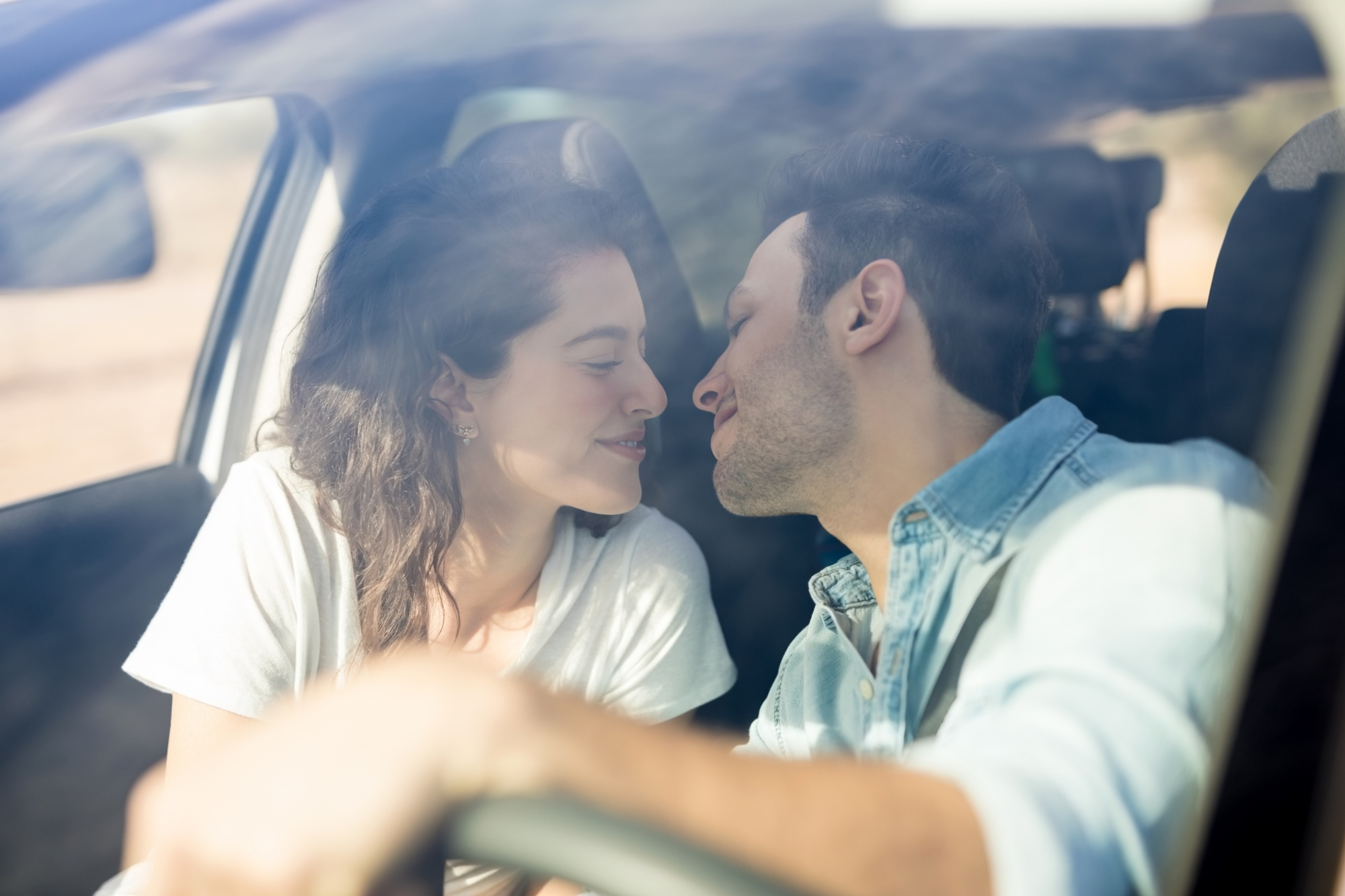 """Let's Talk About Sex: When Being Too Busy Interferes With """"Getting Busy"""" Woman and man leaning in to kiss each other in front seat of car"""