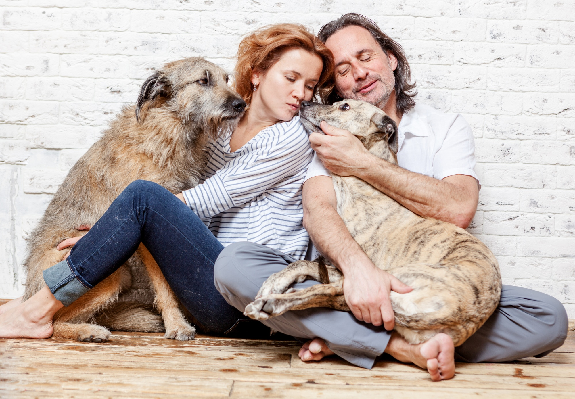 dogs save empty nesters, middle aged couple sitting relaxed on the floor snuggling with their dogs