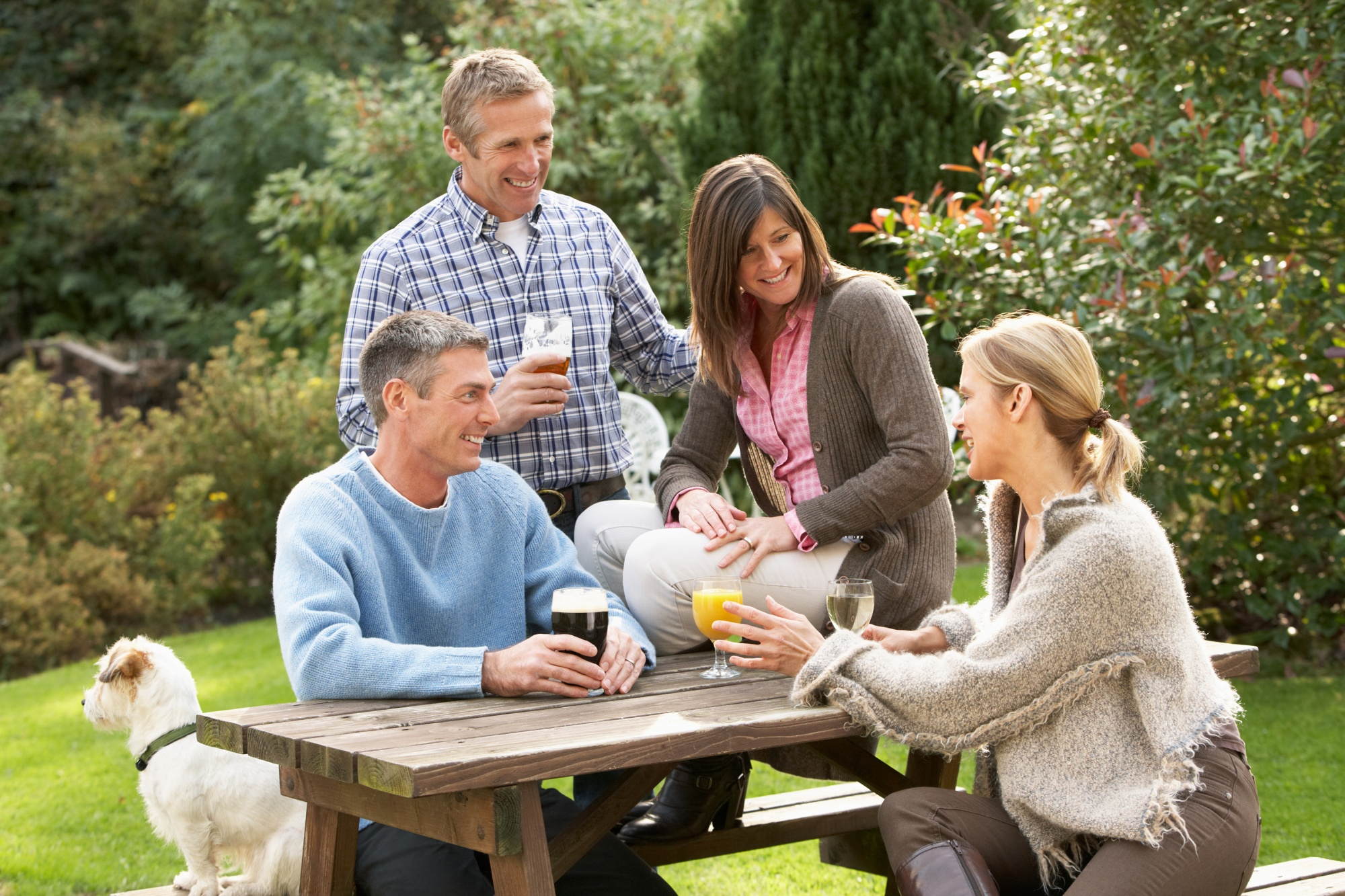 dogs save empty nesters, two couples over 40, friends, sitting outside with their dog smiling and sharing drinks