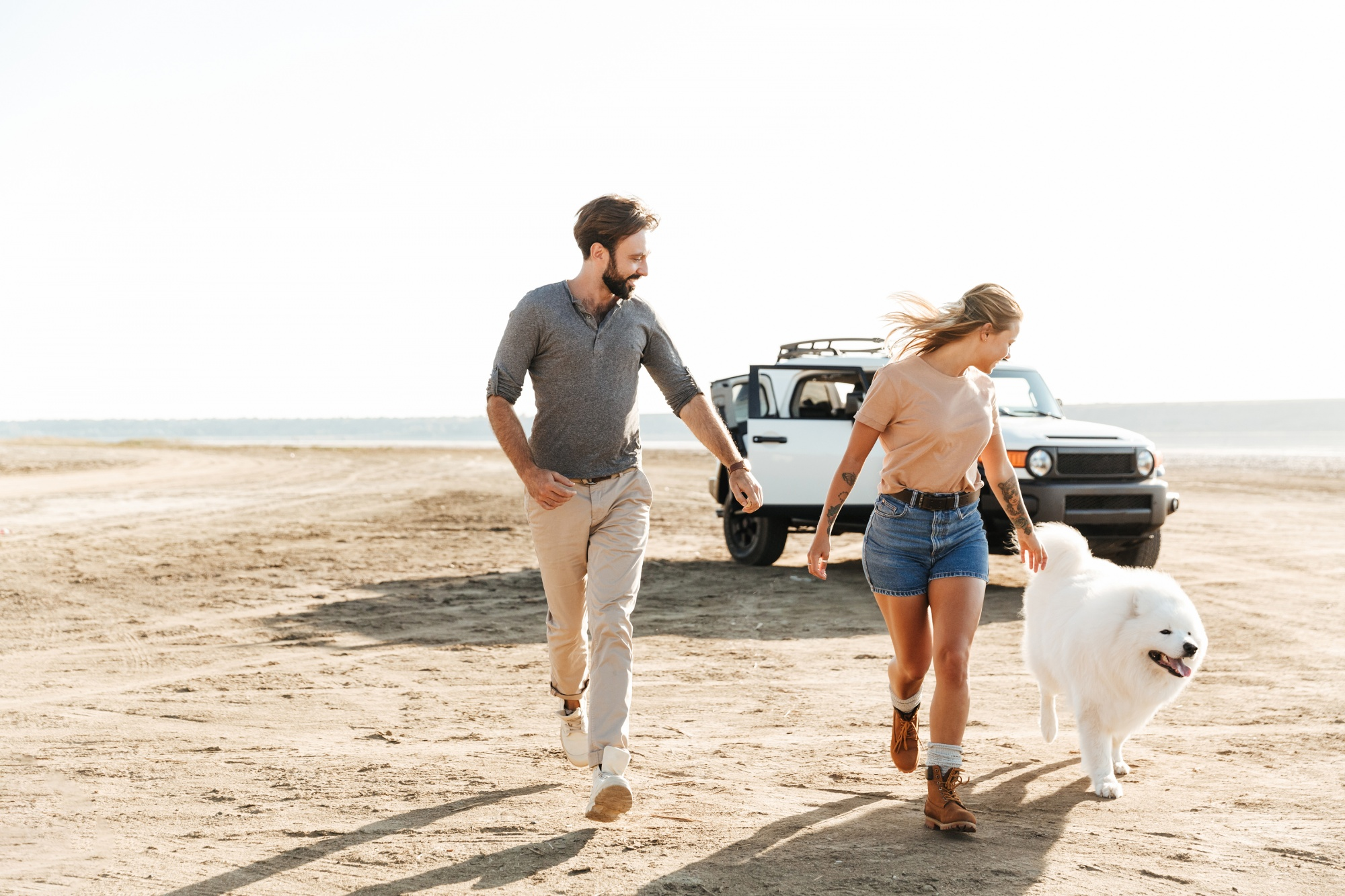 dogs save empty nesters, active couple running with their beautiful white dog on the beach