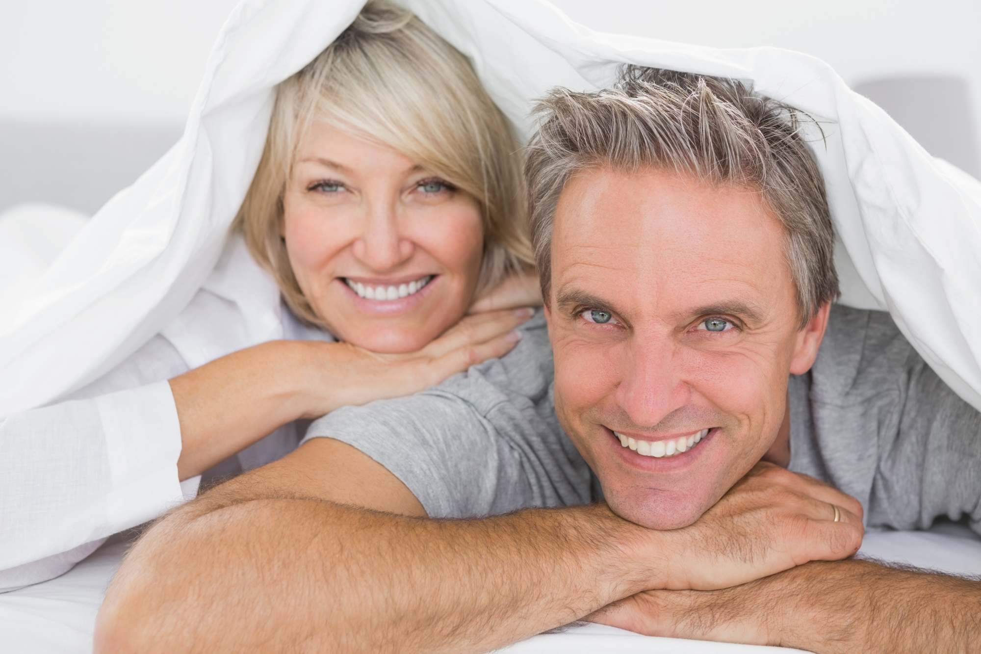 """Let's Talk About Sex: When Being Too Busy Interferes With """"Getting Busy"""". Man and woman happy in bed together."""