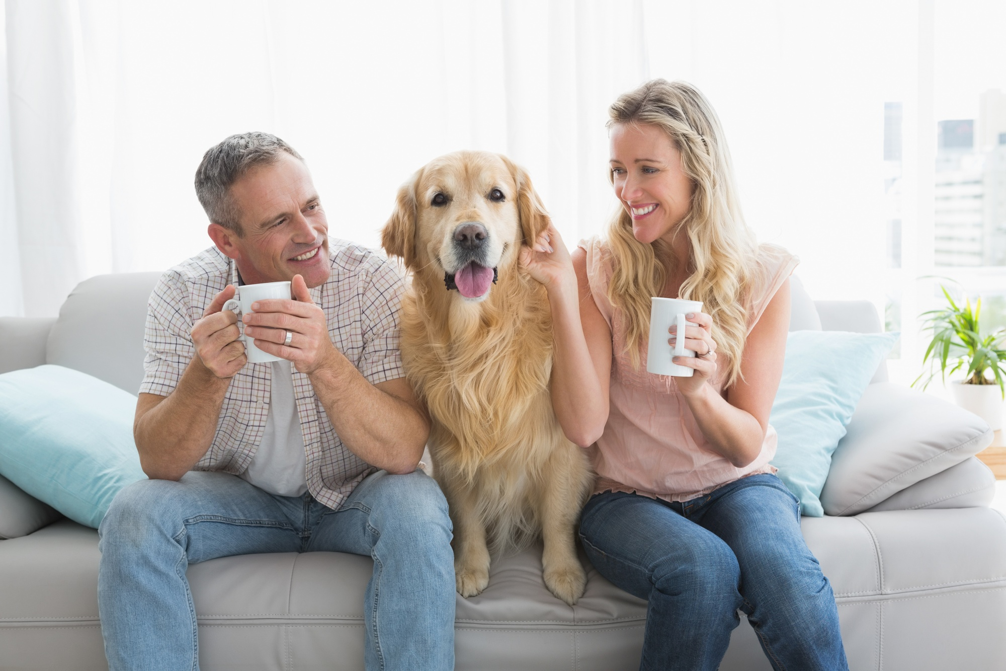 dogs save empty nesters, attractive couple over 40 sitting on the sofa drinking coffee with their golden retriever