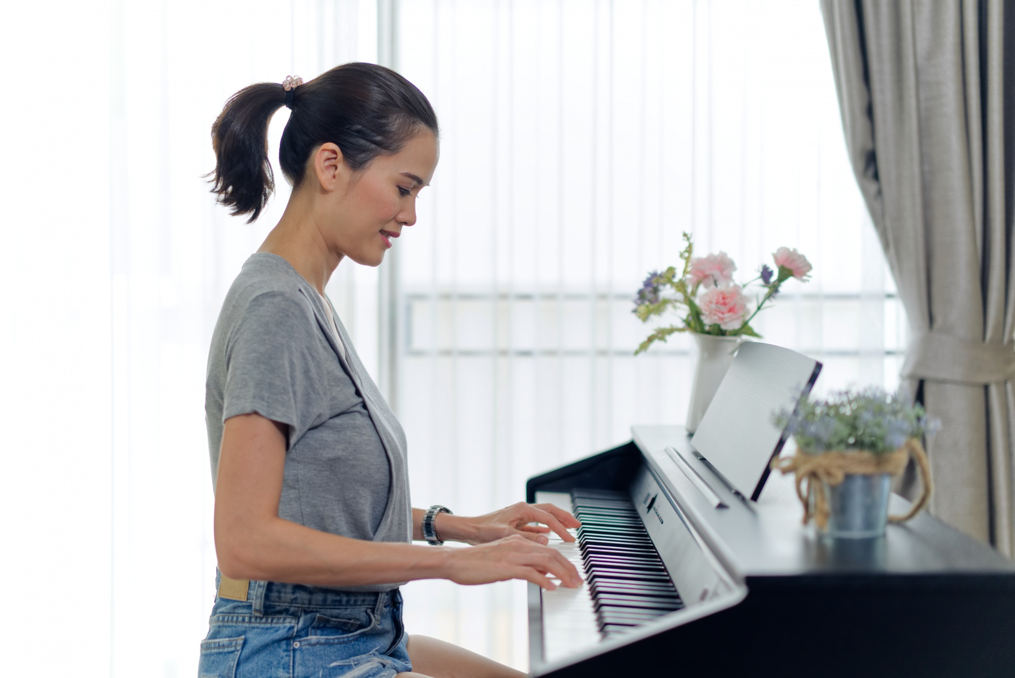 What is neuroplasticity? Asian woman in denim shorts and grey tank playing piano